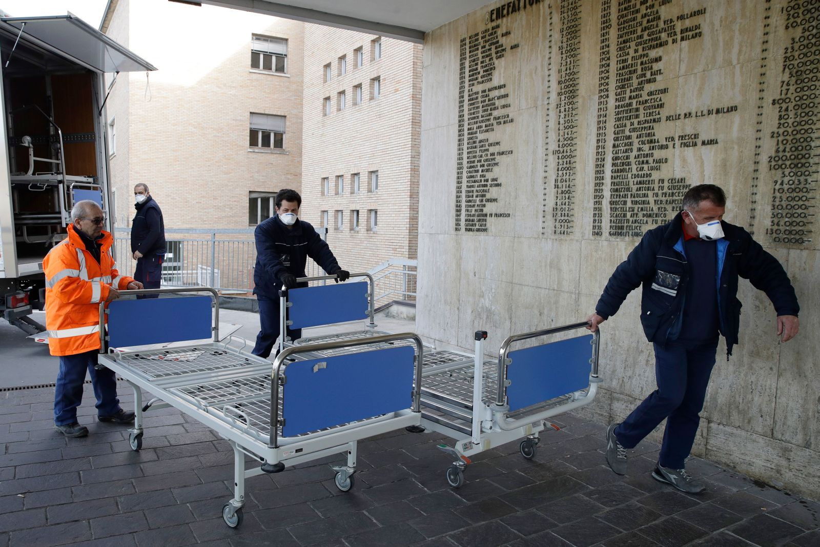Hospital personnel in Codogno, Italy, carry new beds inside the hospital on February 21.