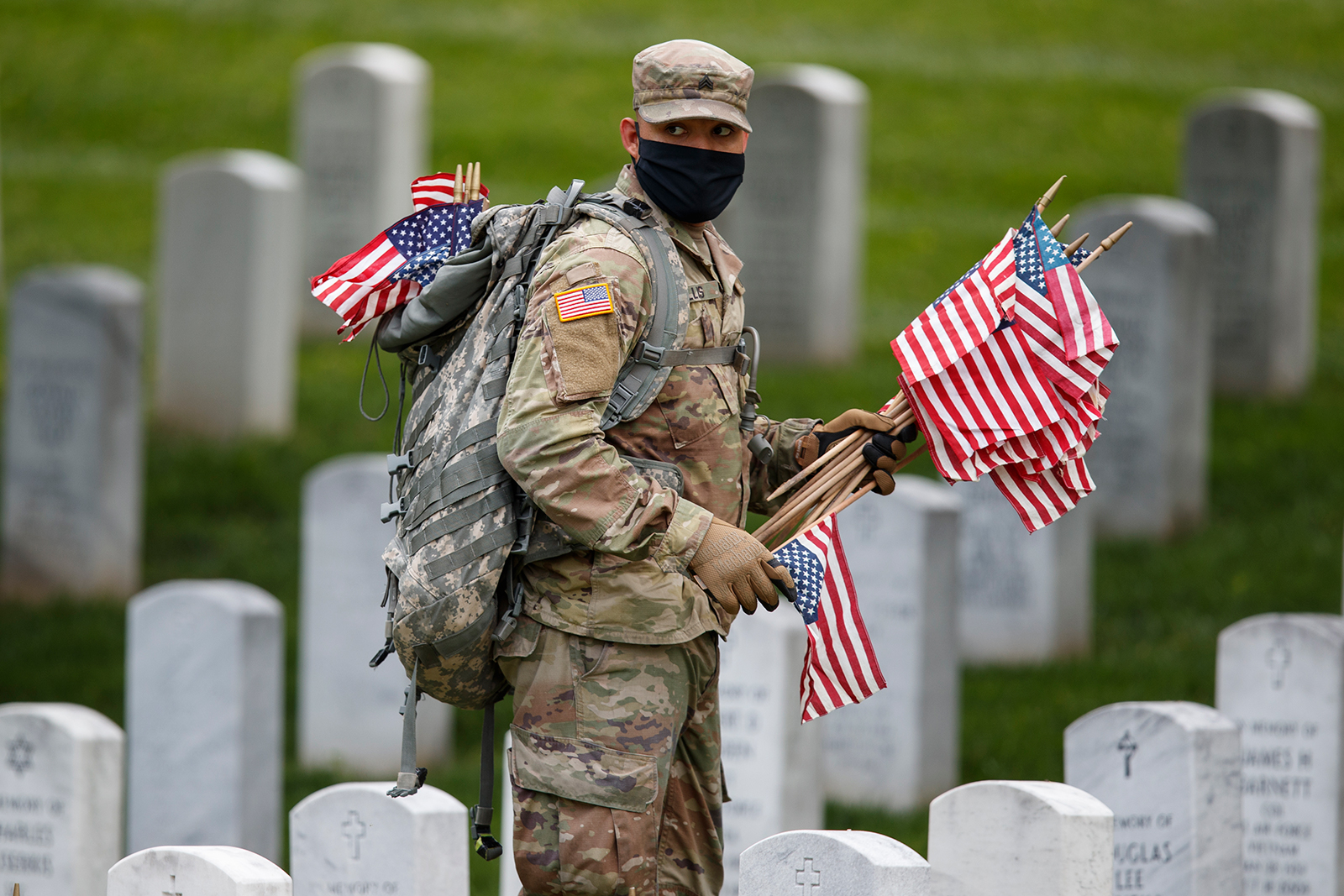"Wearing a face mask, a member of the 3rd U.S. Infantry Regiment places flags in front of each headstone for ""Flags-In"" at Arlington National Cemetery in Arlington, Virginia on May 21."