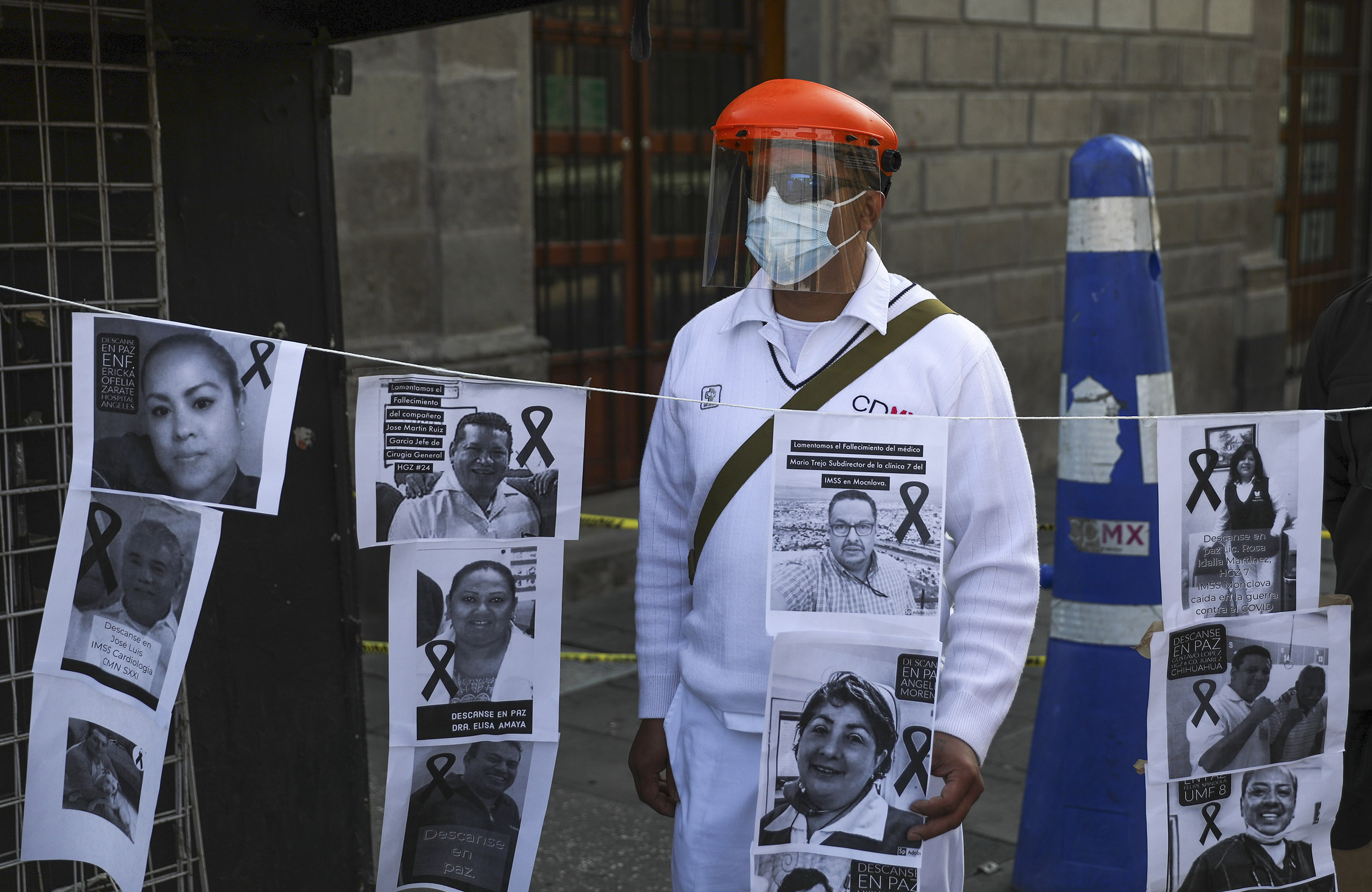 A hospital worker stands with images of colleagues who have died from Covid-19 during a protest in front of the National Palace in Mexico City on May 29.