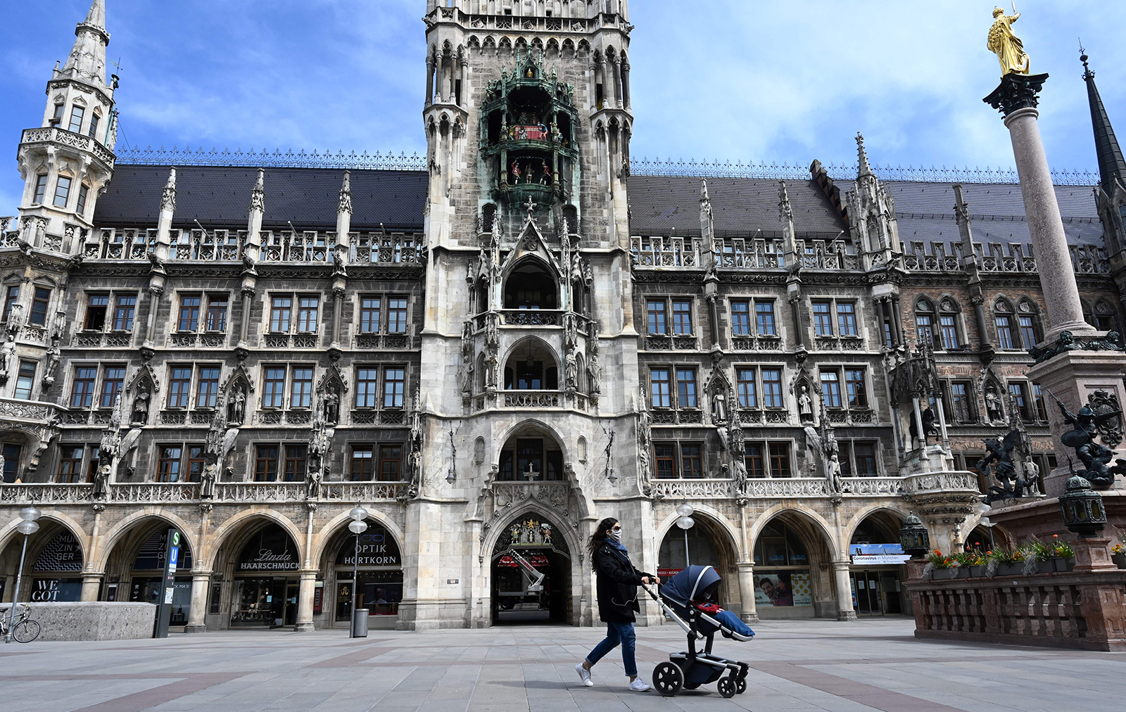 A woman pushing a stroller walks at the empty Marienplatz in Munich on April 21.