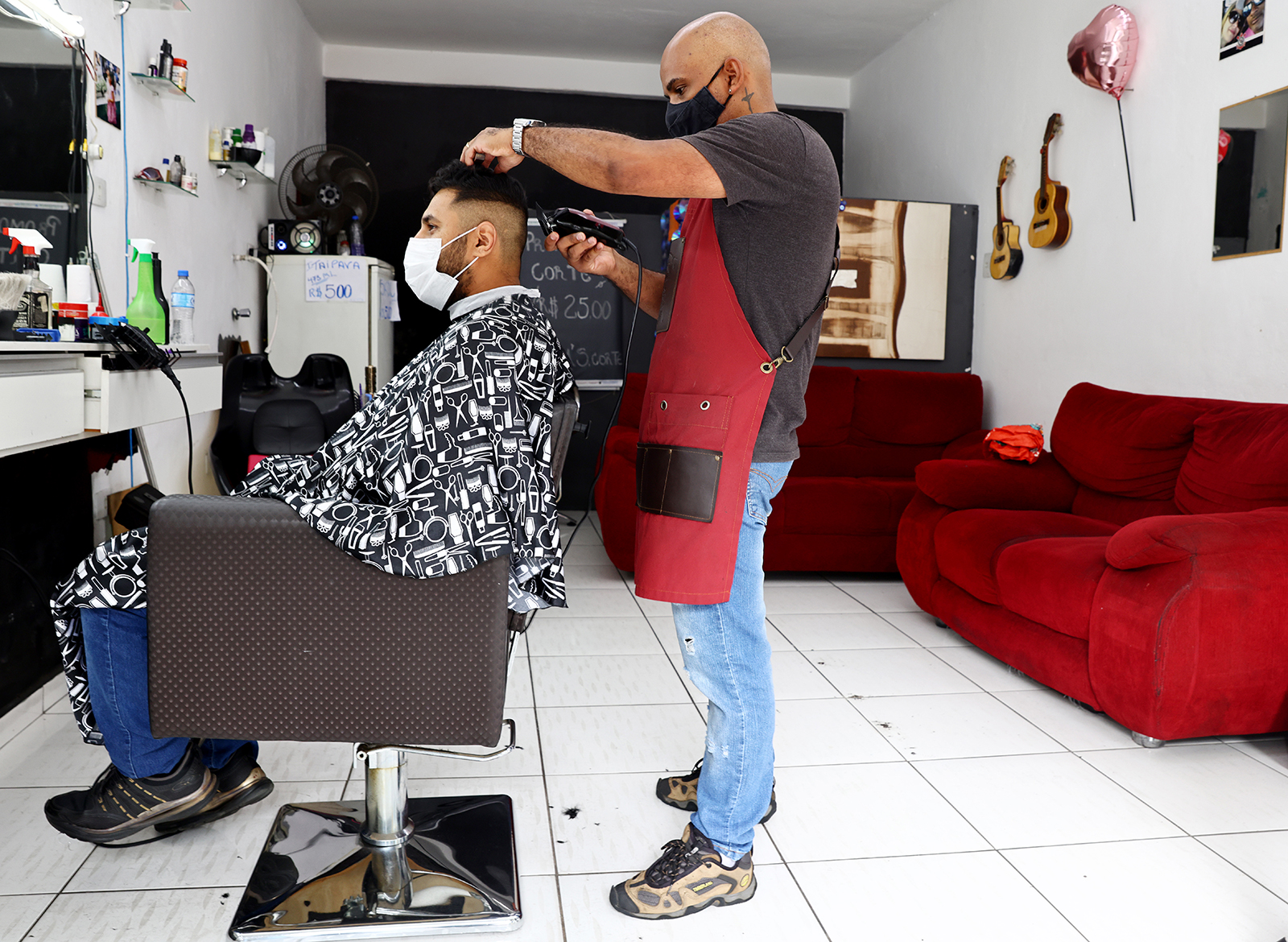 A barber cuts the hair of a client in his barbershop in the Brasilandia neighborhood amid the pandemic on May 15, in Sao Paulo, Brazil.