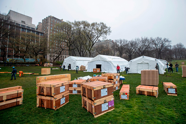 A Samaritan's Purse crew works on building an emergency field hospital equipped with a respiratory unit in New York's Central Park across from the Mount Sinai Hospital, Sunday, March 29.