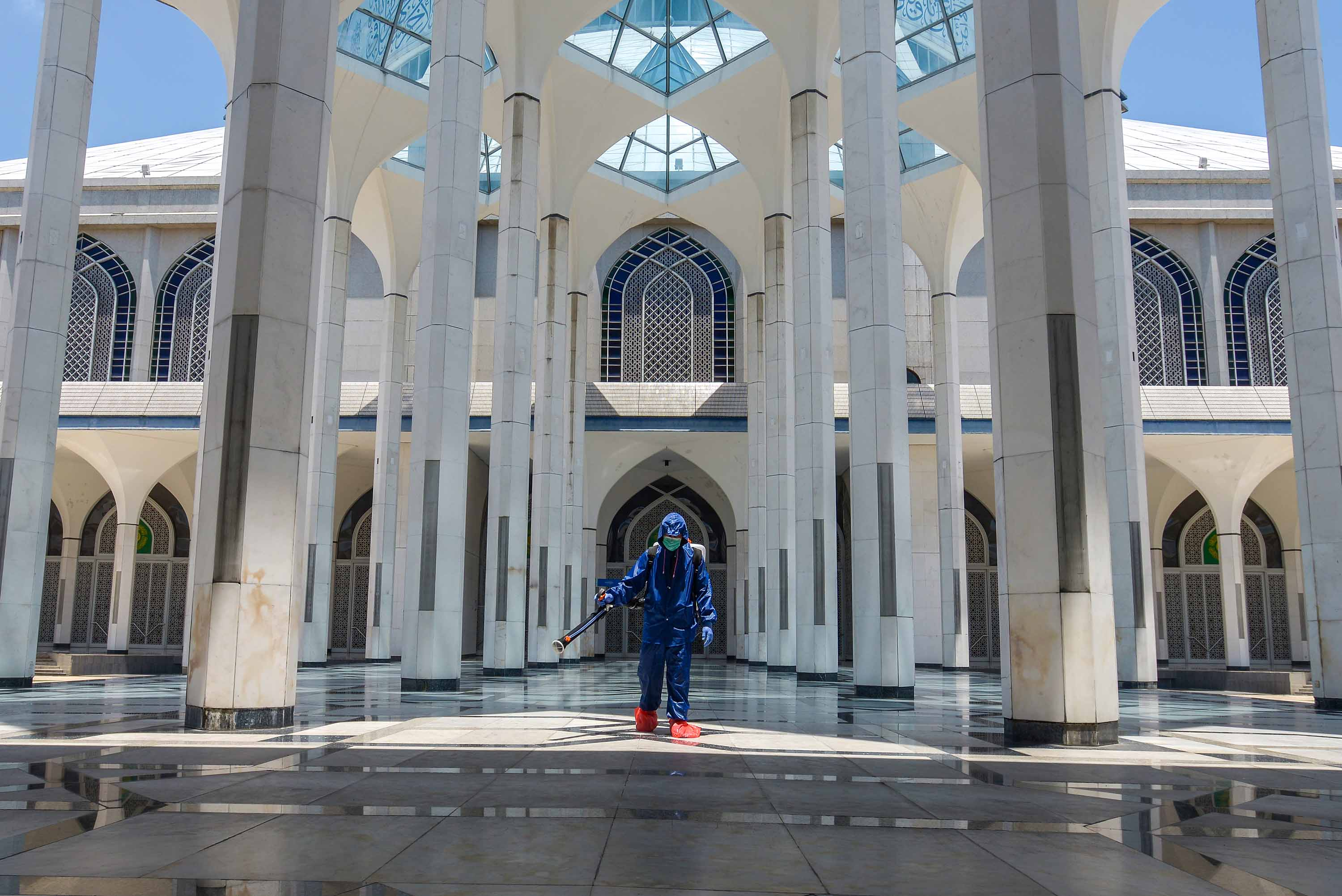 A worker sprays disinfectant at a mosque in Shah Alam, Malaysia on March 26.