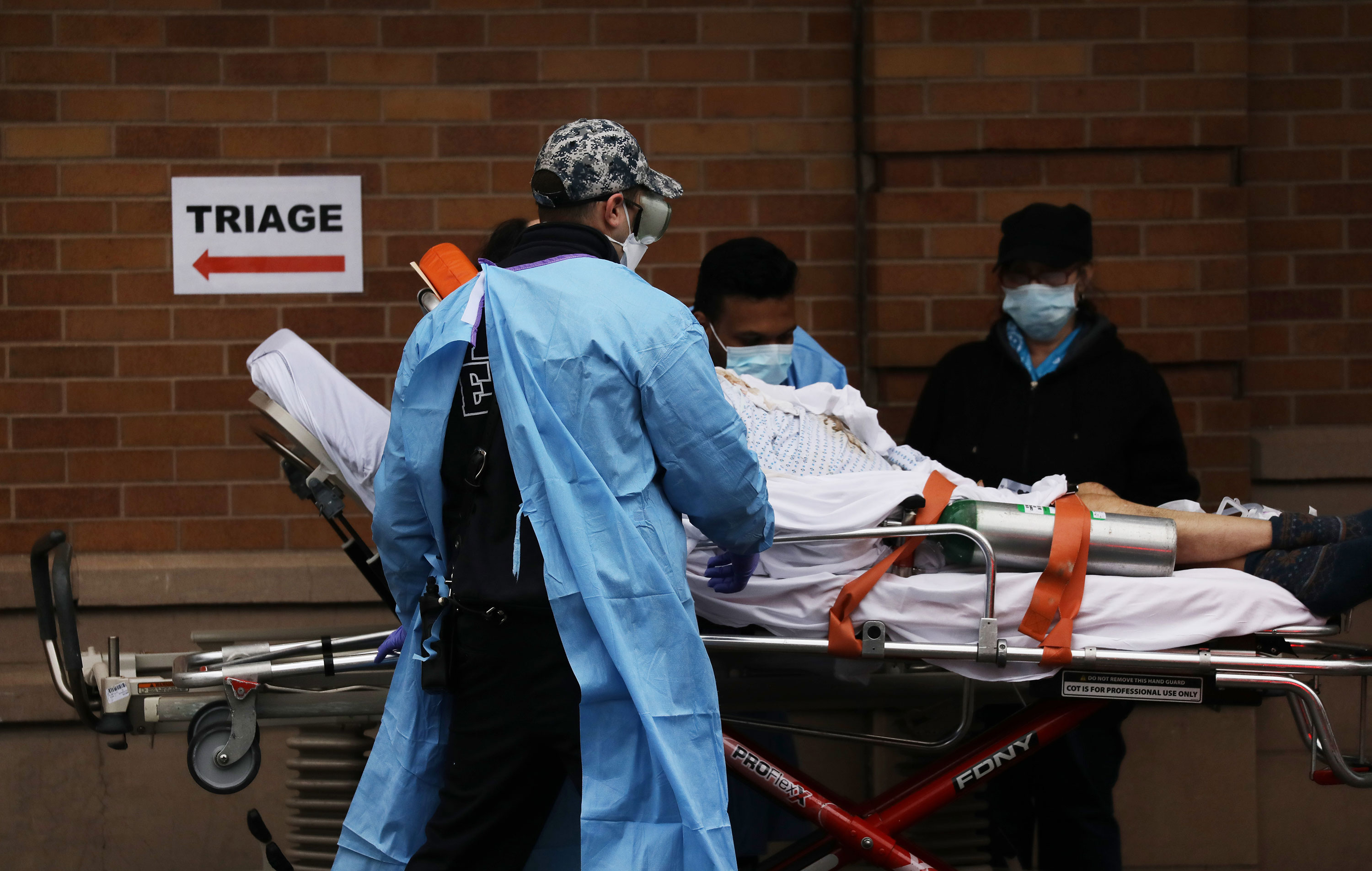 Medical workers move a patient to a special coronavirus intake area at Maimonides Medical Center in Brooklyn, New York on April 3.