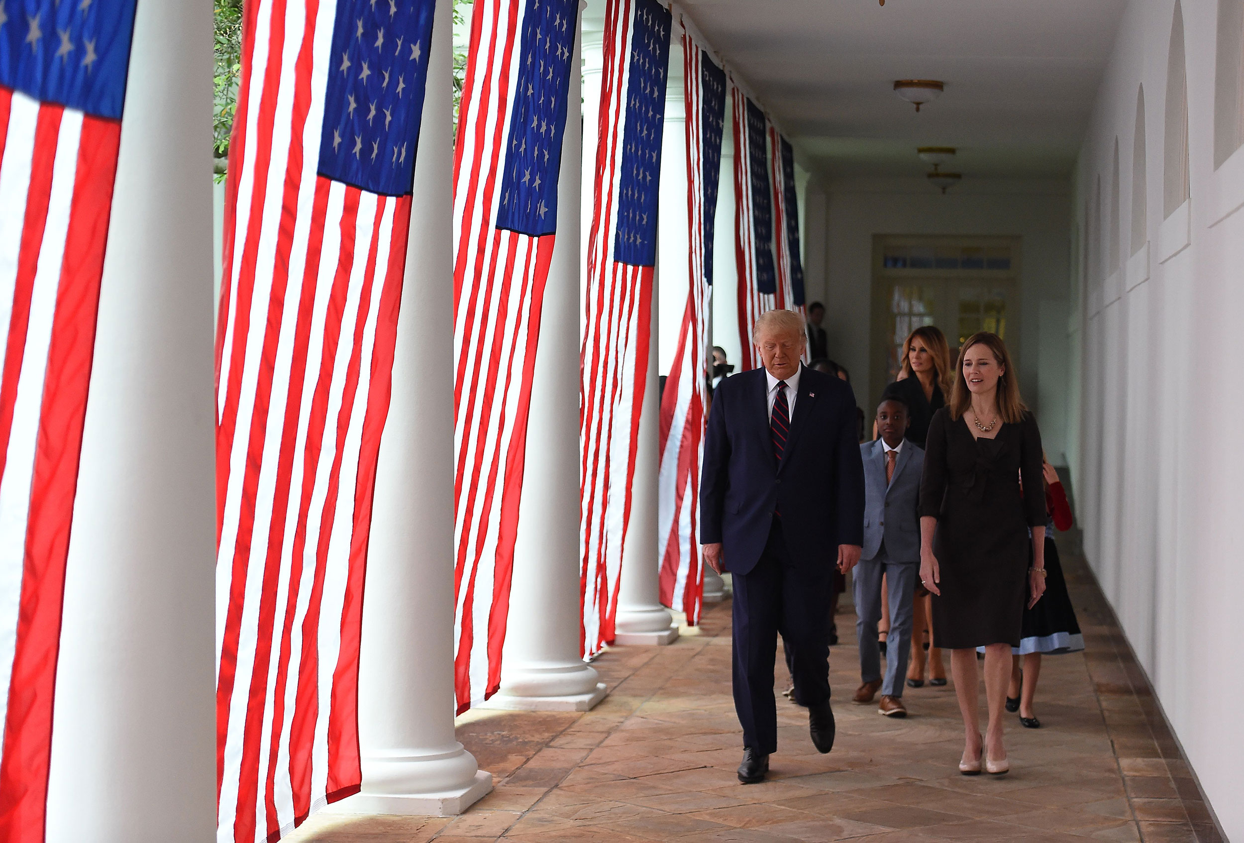 President Donald Trump and Amy Coney Barrett walk to the Rose Garden on Saturday.