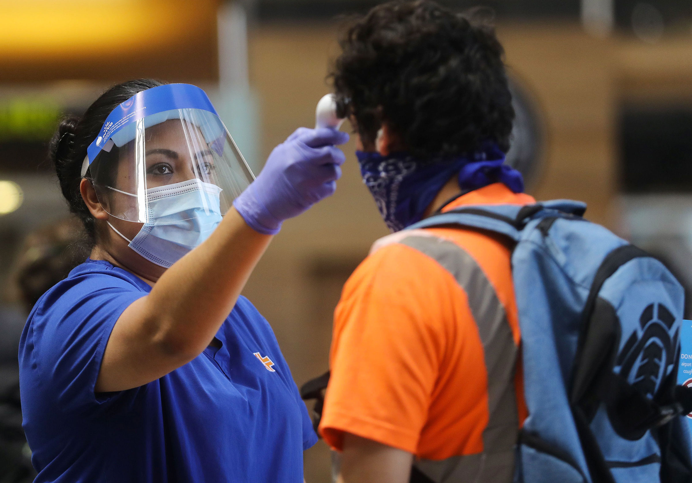 A traveler is checked with a handheld thermometer at Los Angeles International Airport on June 24 in Los Angeles, California.