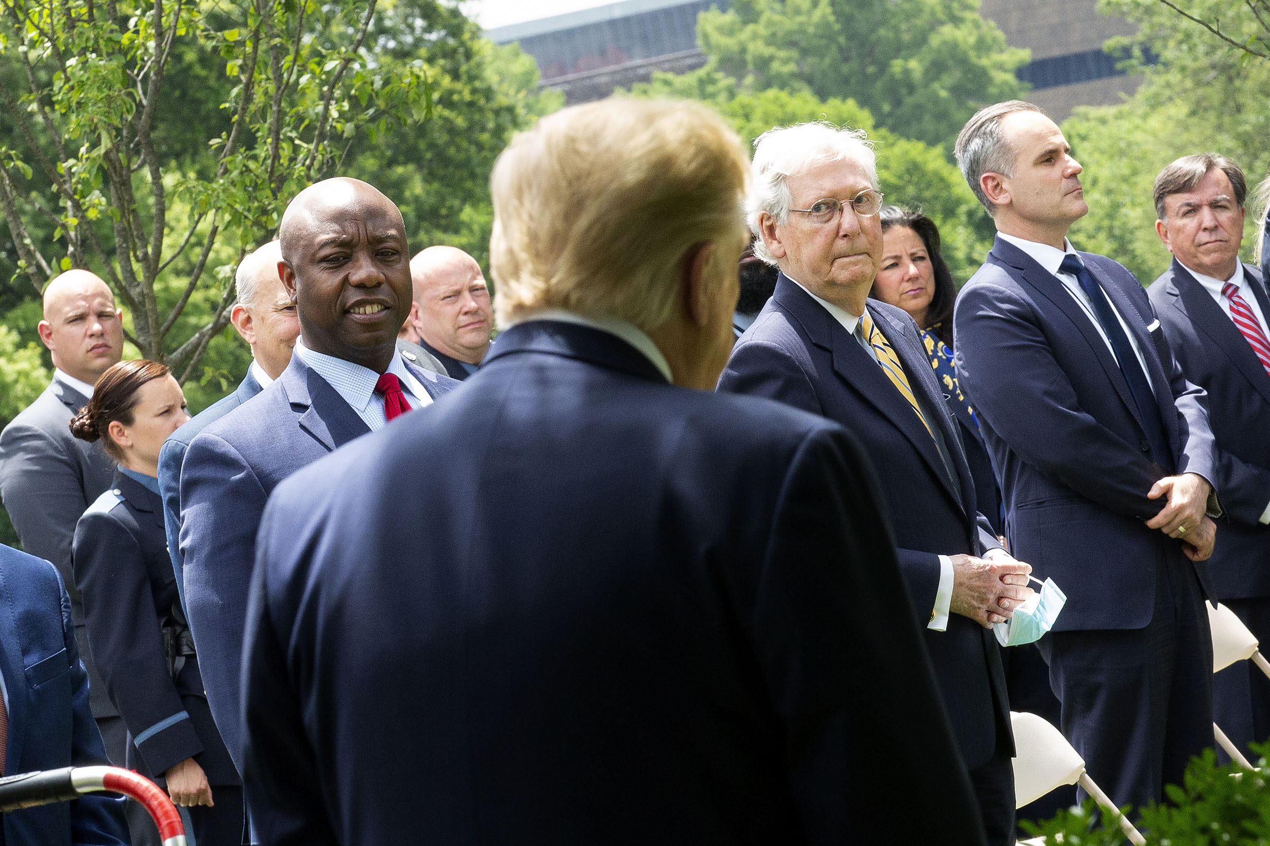 Sen. Tim Scott (R-S.C.), left, and Sen. Majority Leader Mitch McConnell (R-Ky.), right, look towards US President Donald Trump as he arrives to the Rose Garden to sign an Executive Order on Safe Policing for Safe Communities in the Rose Garden of the White House in Washington DC, on Tuesday, June 16.