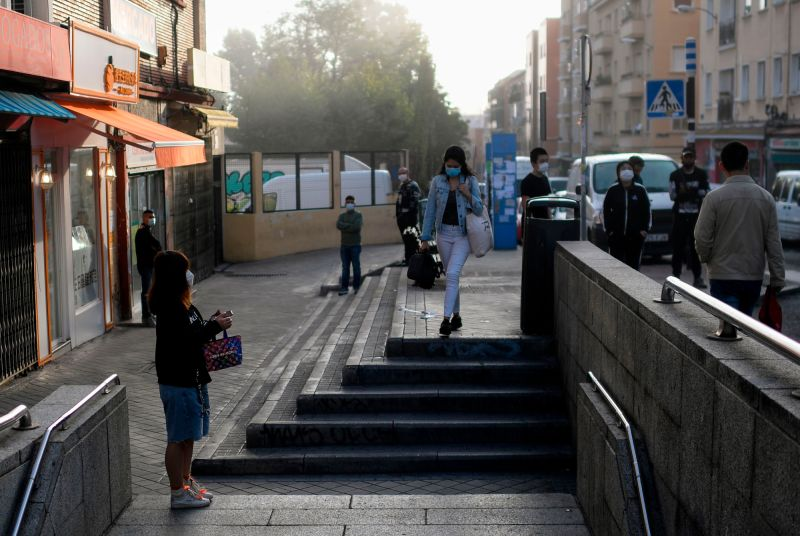 People stand outside a metro station in Madrid early on September 21.