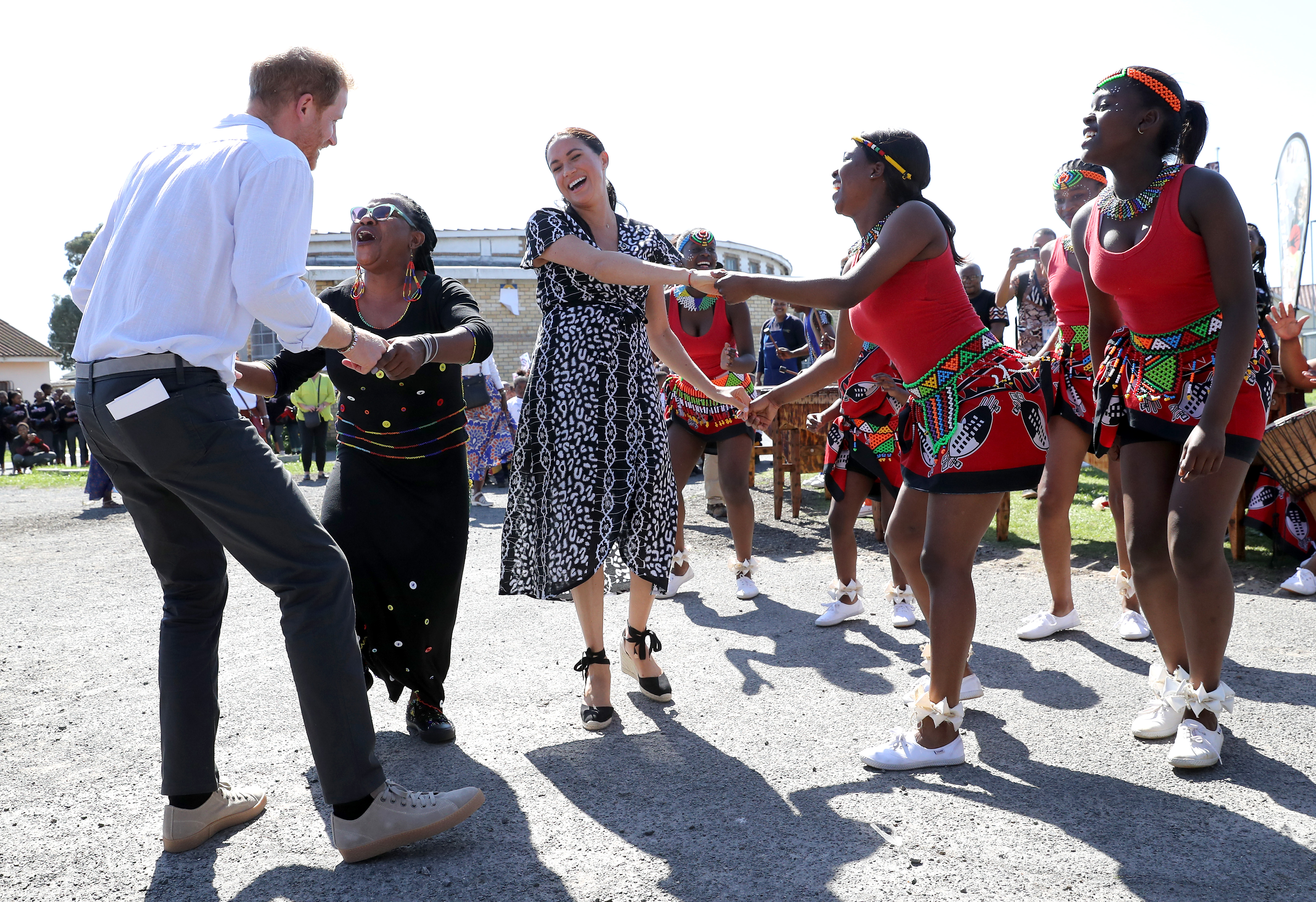 Prince Harry, Duke of Sussex and Meghan, Duchess of Sussex dance with a group of performers at their first engagement in South Africa after touching down in Cape Town on Monday.