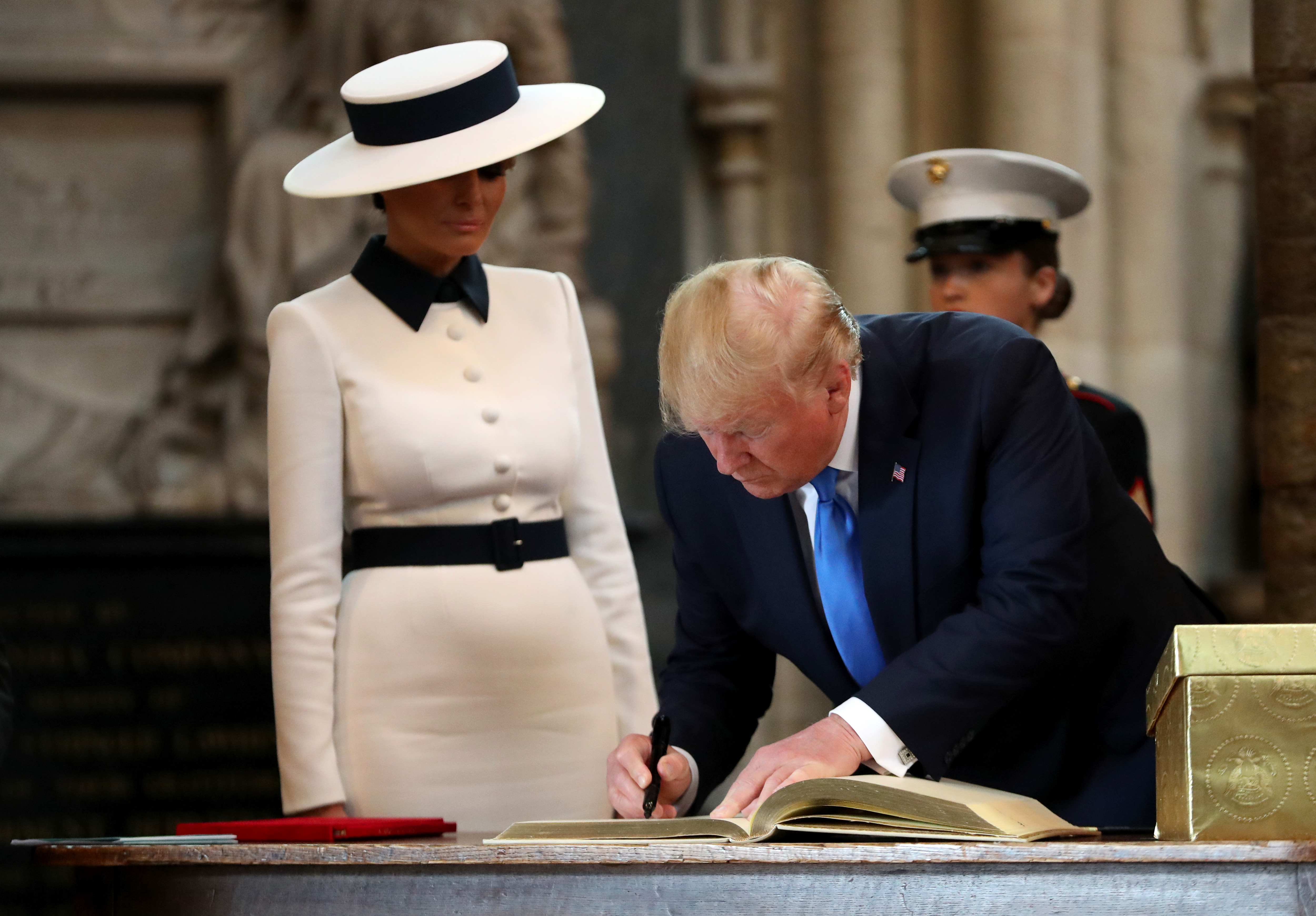 Trump signs the visitors book during the visit to Westminster Abbey with First Lady Melania Trump on Monday in London.