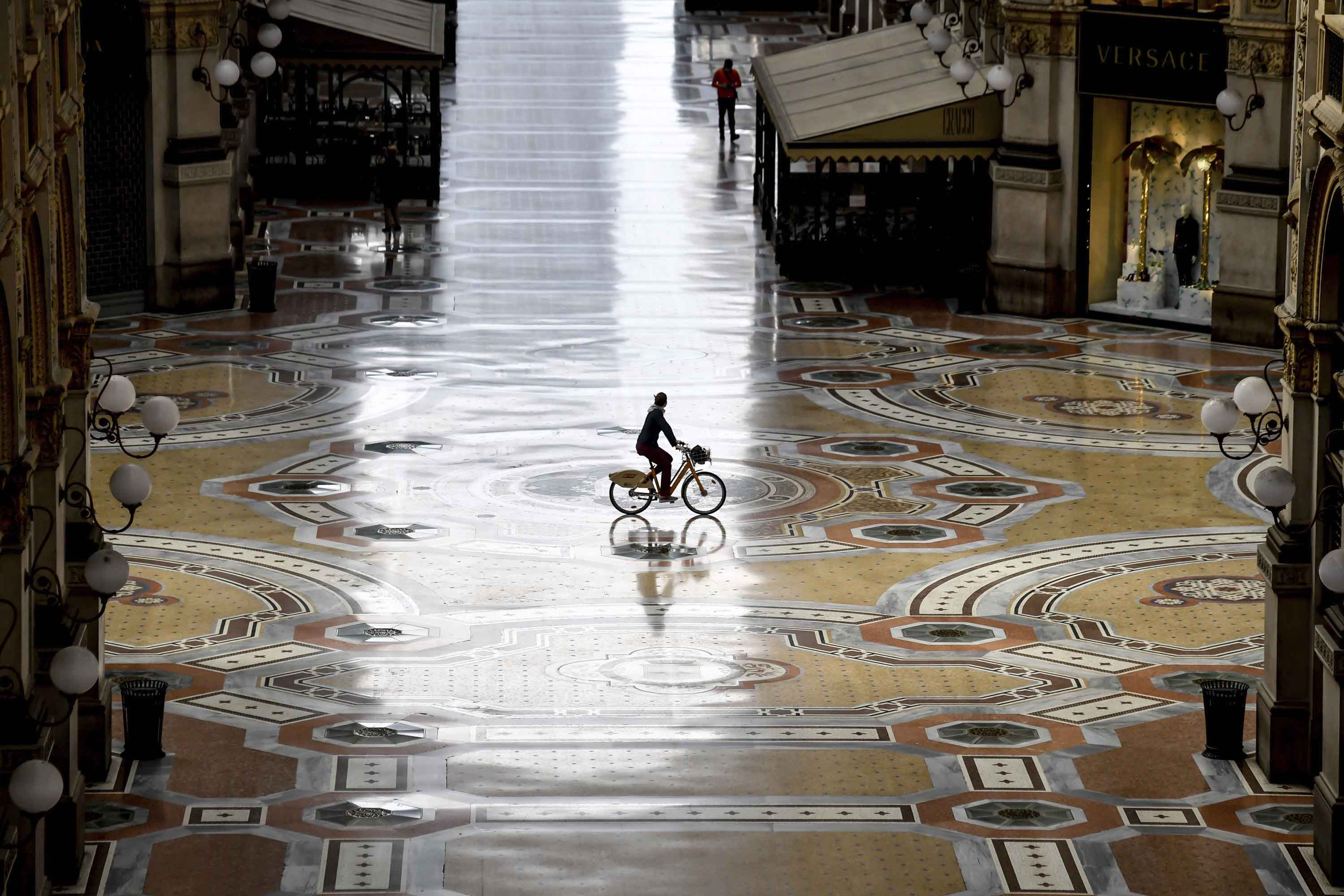 A cyclist rides along an empty Galleria Vittorio Emanuele II shopping arcade during Italy's continued lockdown in Milan on Thursday, April 30.