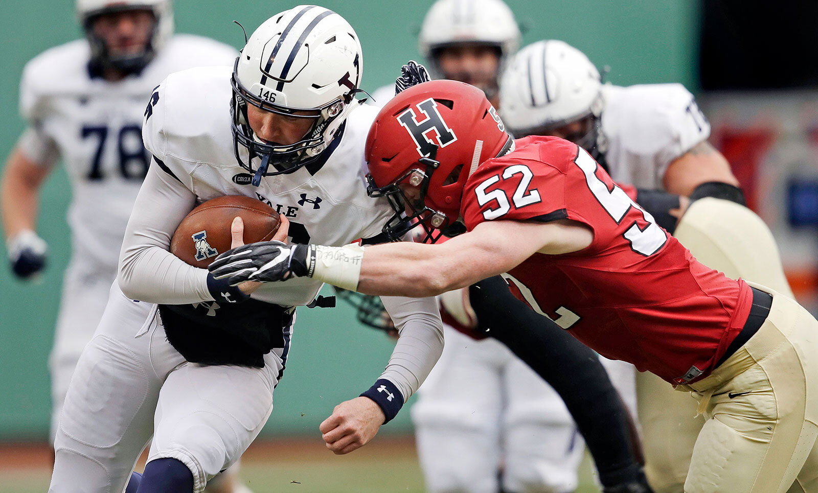 In this November 17, 2018 file photo, Yale quarterback Griffin O'Connor, left, tries to elude Harvard linebacker Cameron Kline (52) while scrambling for a gain during the first half of an NCAA college football game at Fenway Park in Boston.