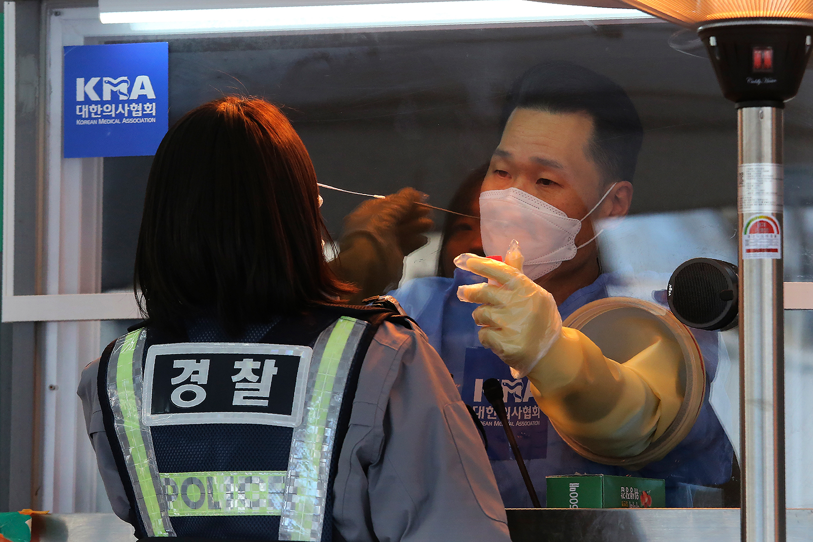 A medical worker in a booth takes nasal samples from a police officer at a coronavirus testing site in Seoul, South Korea, on January 8.