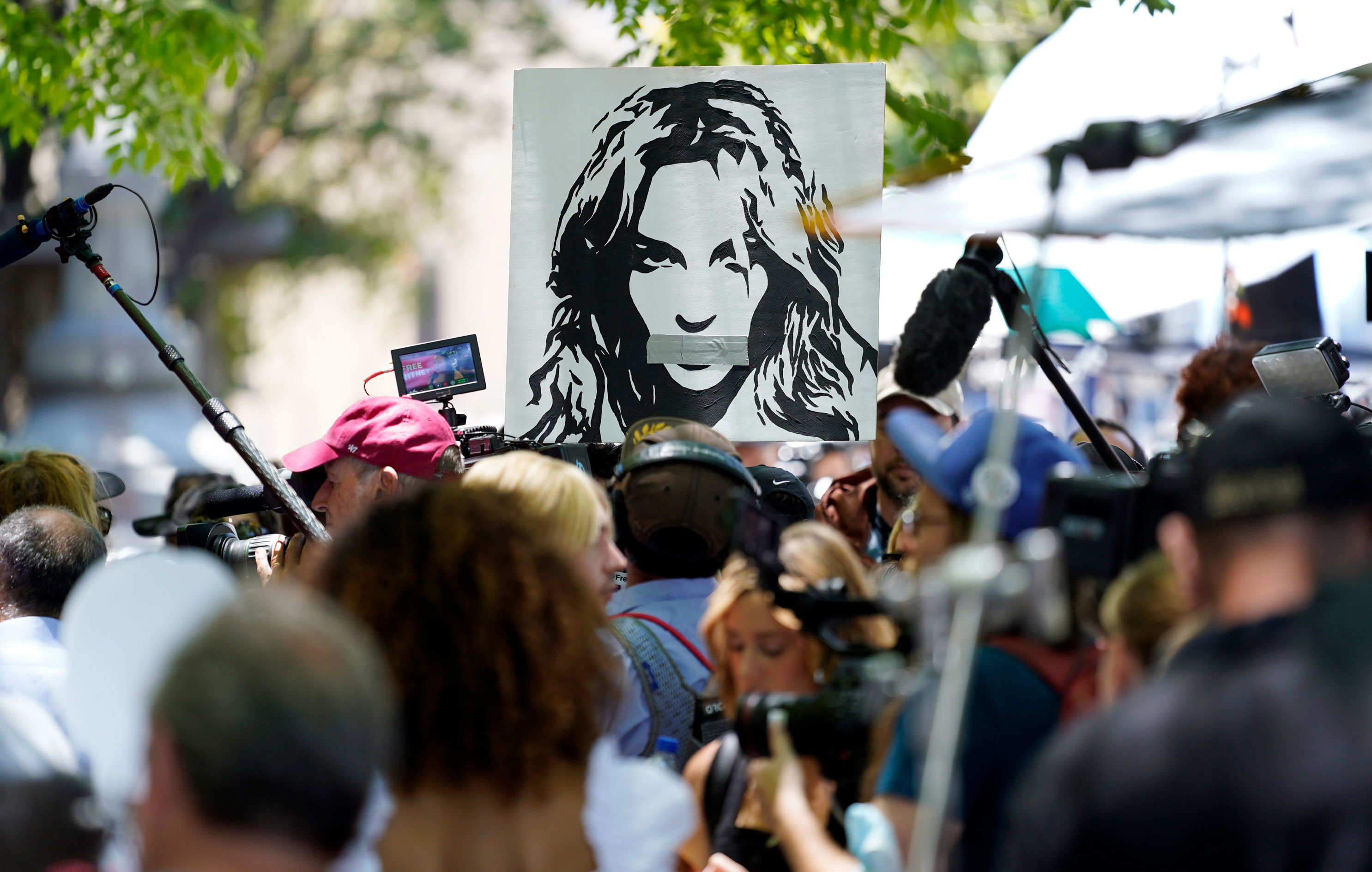 A portrait of Britney Spears looms over supporters and media members outside a court hearing concerning the pop singer's conservatorship at the Stanley Mosk Courthouse, on Wednesday, June 23, in Los Angeles.