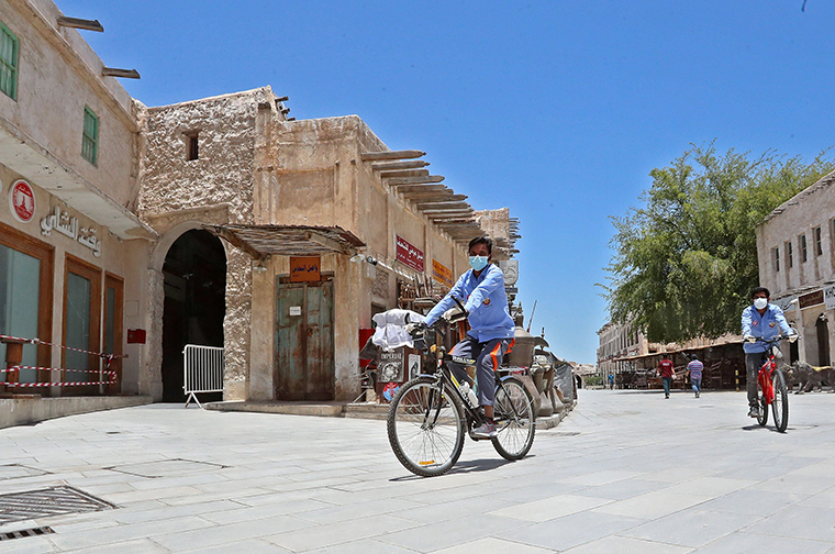 Workers wearing masks ride bicycles at Qatar's touristic Souq Waqif bazar in the capital Doha, on Sunday, May 17, as the country begins enforcing the world's toughest penalties for failing to wear masks.