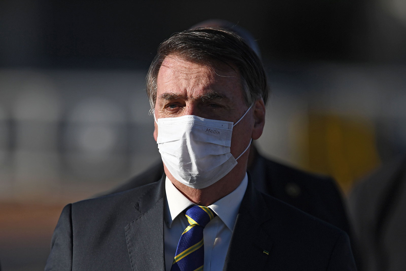 Brazilian President Jair Bolsonaro wears a face mask as he arrives at the flag-raising ceremony before a ministerial meeting at the Alvorada Palace in Brasilia, on May 12.