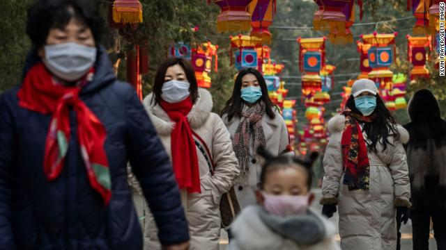 Chinese women and a child all wear protective masks as they walk under decorations in a Beijing park.