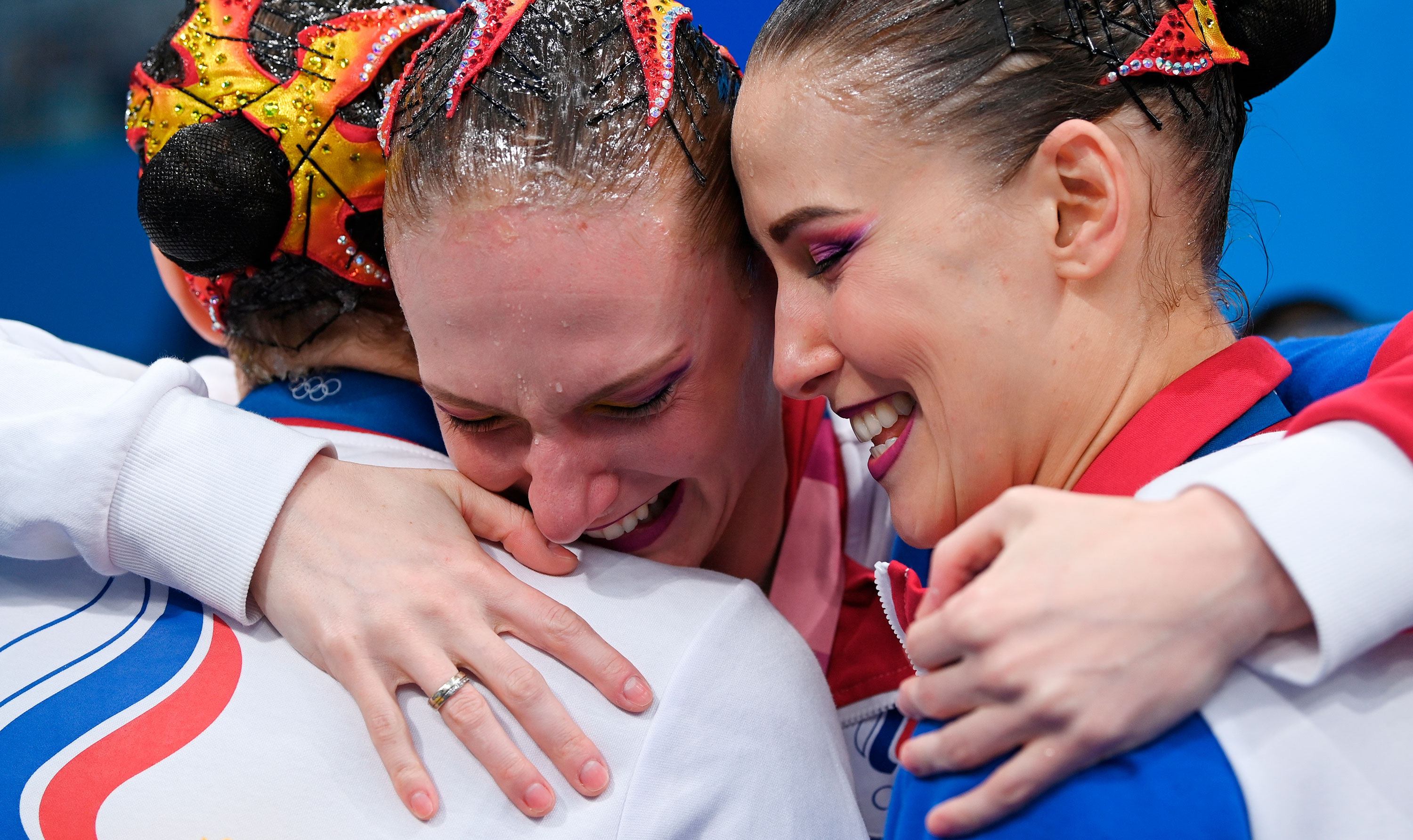 Svetlana Romashina of the Russian Olympic Committee, center, celebrates victory with her teammates after they won gold in the team artistic swimming final.