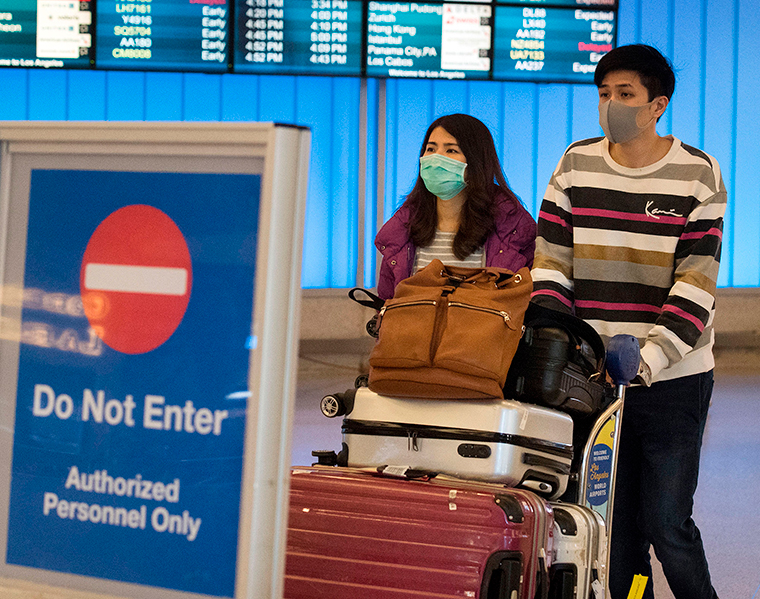 Passengers wear protective masks to protect against the spread of the coronavirus as they arrive at the Los Angeles International Airport  on January 22.