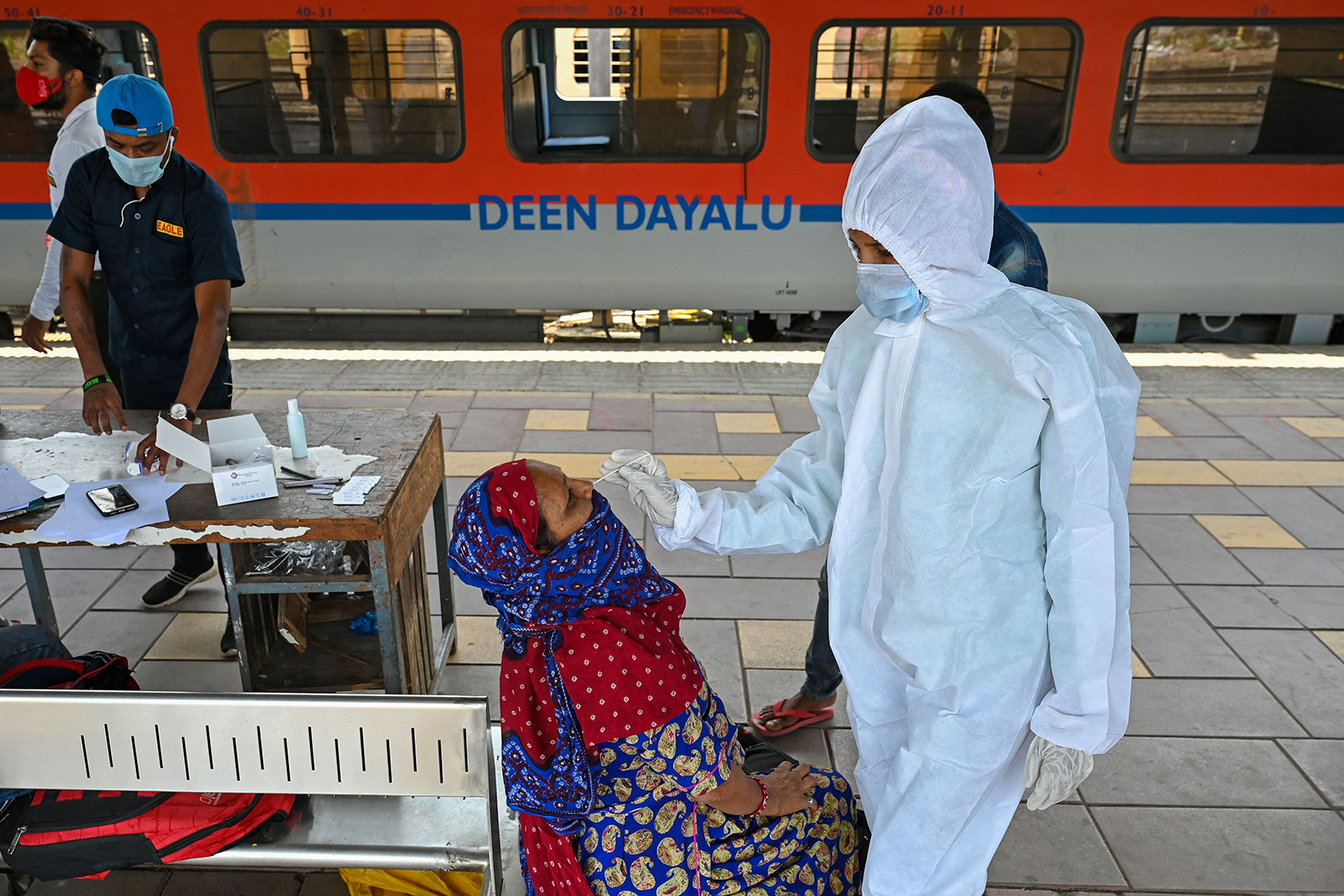 A health worker takes a nasal swab sample from a passenger for a Covid-19 test after arriving at a railway platform, in Mumbai, India, on April 14.