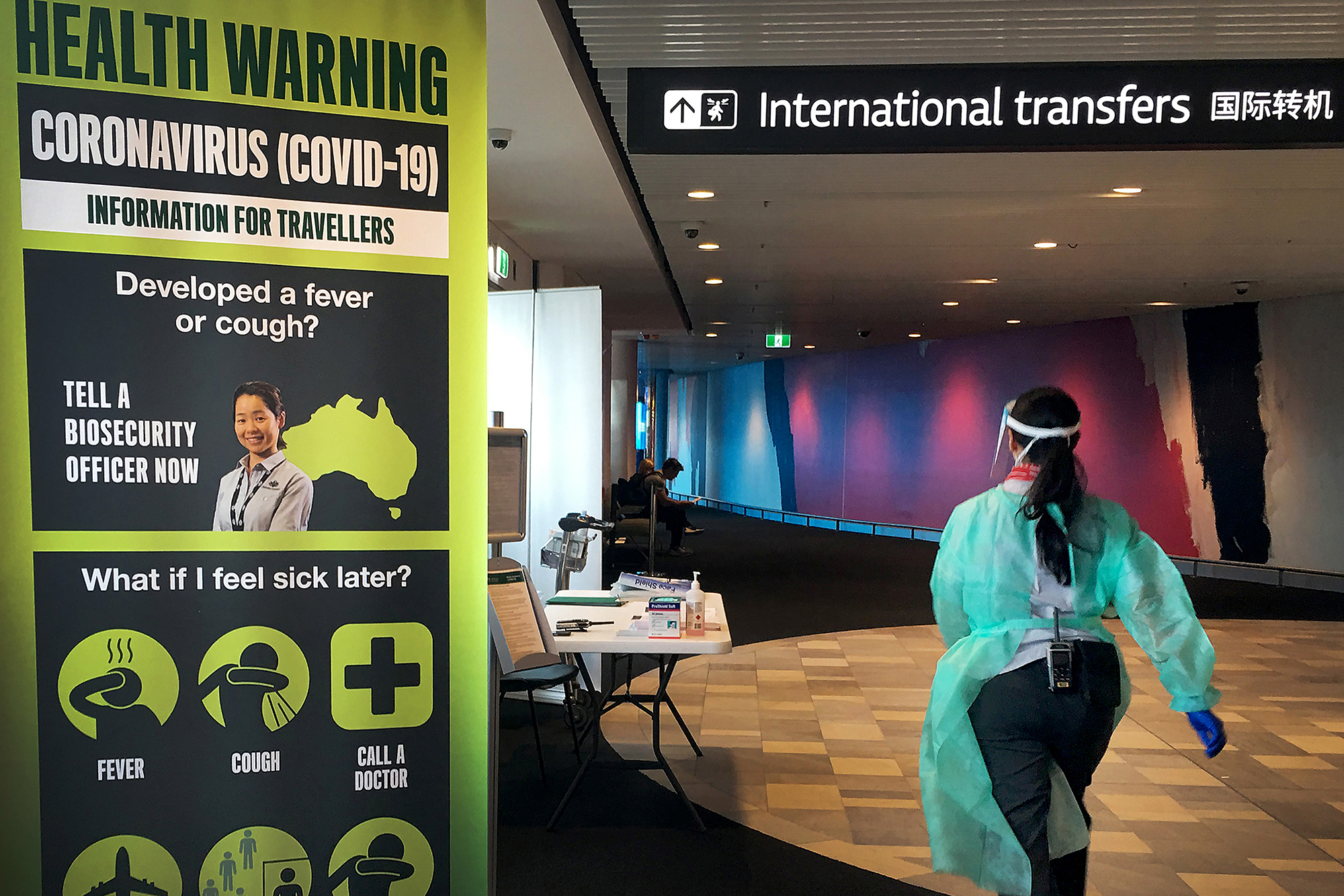 A staff member in protective medical clothing moves through the arrivals area at Brisbane International Airport on March 16 in Brisbane, Australia.