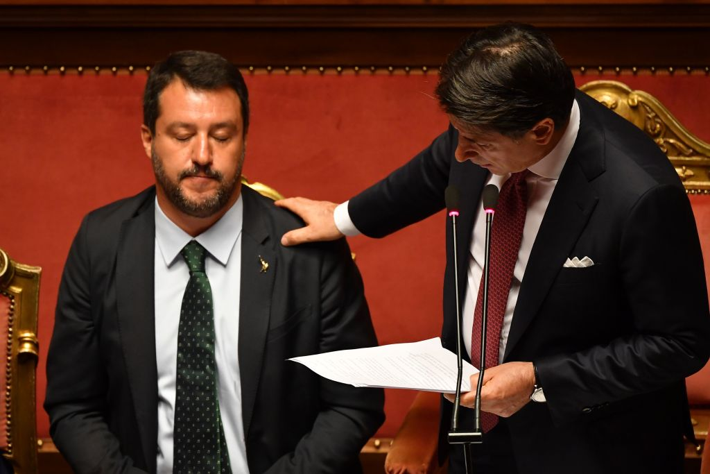 Italian Prime Minister Giuseppe Conte (R) touches Deputy Prime Minister and Interior Minister Matteo Salvini's shoulder as he delivers a speech at the Italian Senate, in Rome, on August 20, 2019, as the country faces a political crisis.