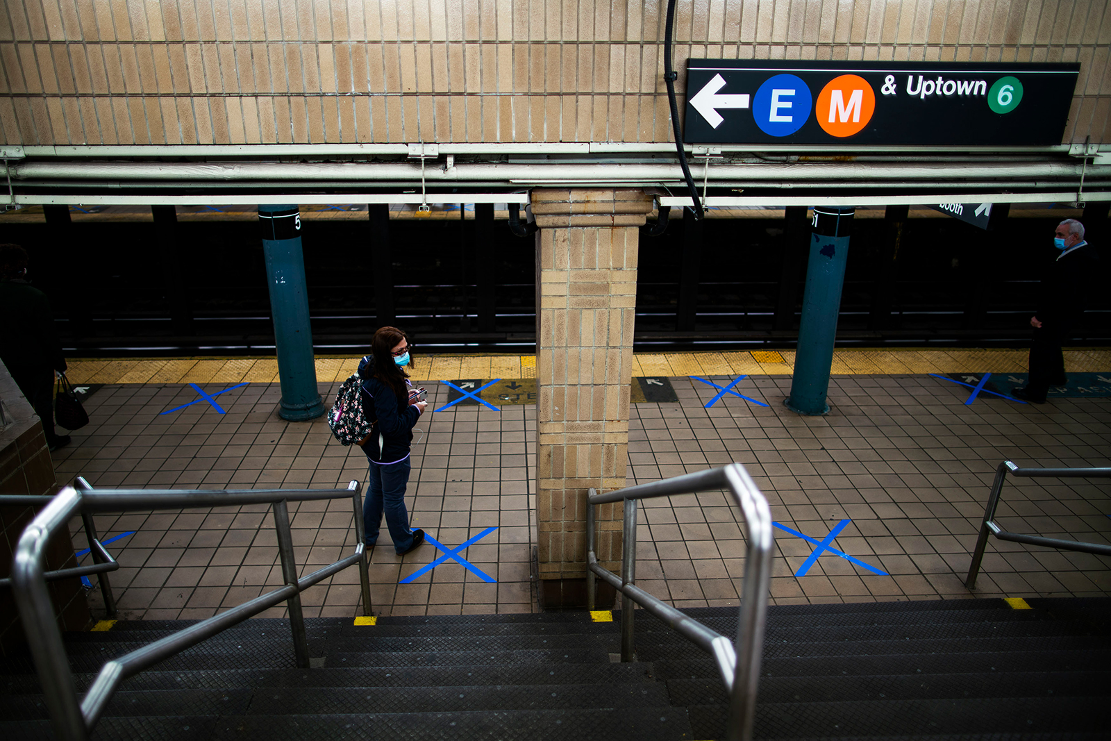 People wearing protective face masks practice social distancing as they wait on marked spots at a subway station during the Covid-19 pandemic on May 12, in New York City.