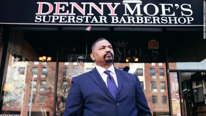 """Dennis """"Denny Moe"""" Mitchell, 54, stands outside of Denny Moe's Superstar Barbershop in Harlem, New York, in an undated photo."""