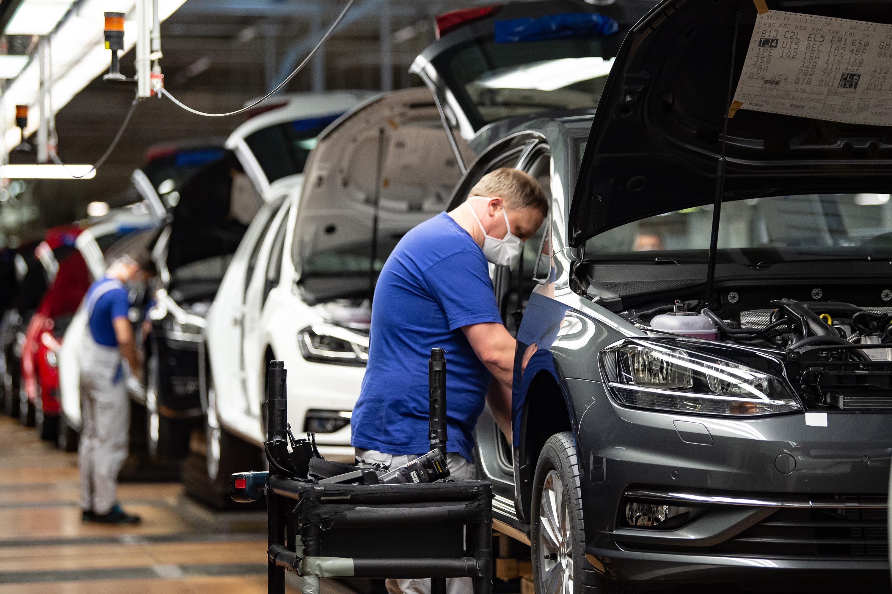 An employee works on a production line after Volkswagen's Wolfsburg Plant reopened on April 27, in Wolfsburg, Germany.