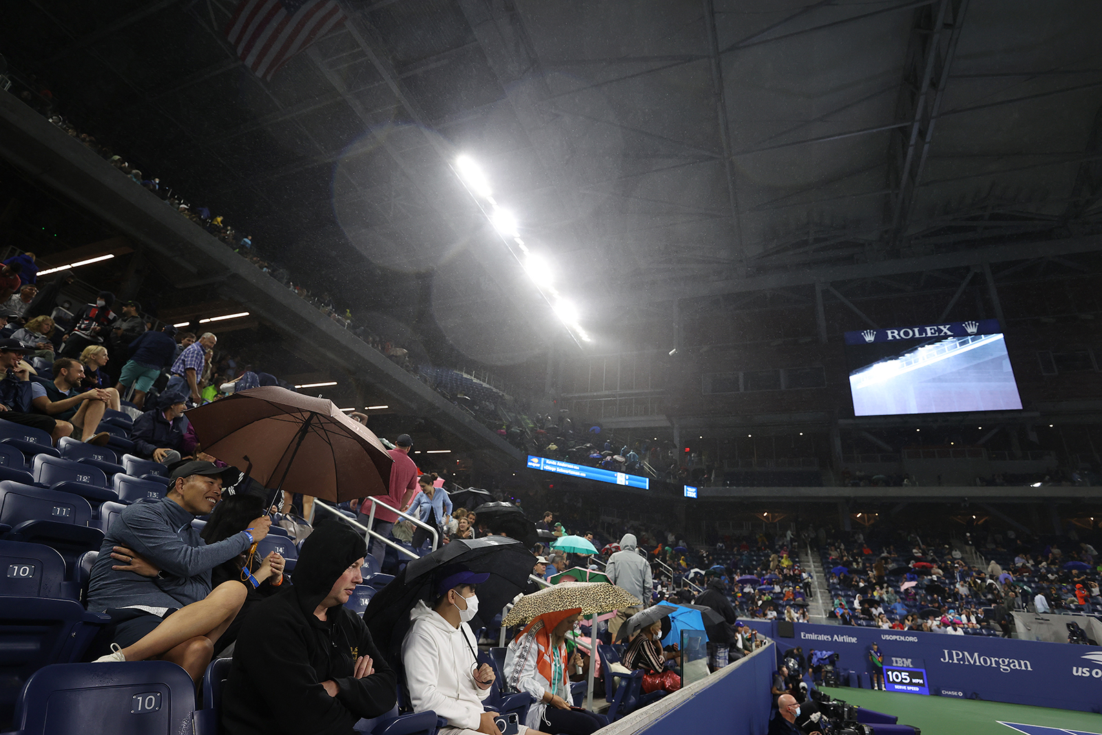 Rain enters the court through the outer openings of the roof causing a delay during the match between South Africa's Kevin Anderson and Argentina's Diego Schwartzman at the 2021 US Open on September 1 in New York.