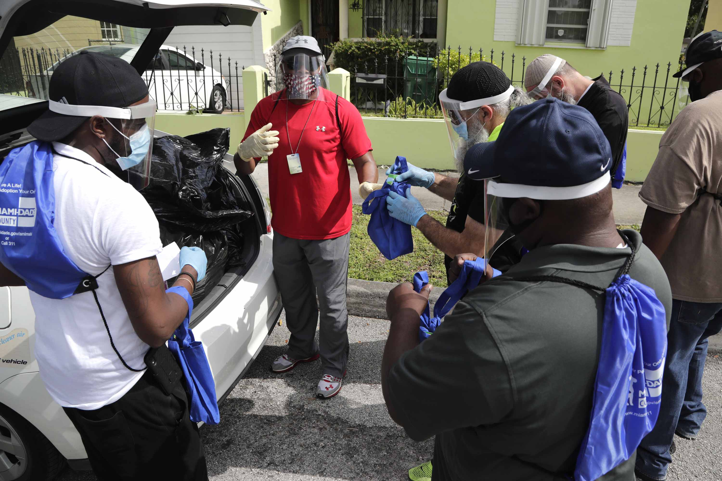 Morris Copeland of the Strategic Urban Response to Guideline Education (SURGE) group, center, passes out coronavirus prevention kits to team members, for distribution to residents living in COVID-19 hotspots in Miami, on July 1.