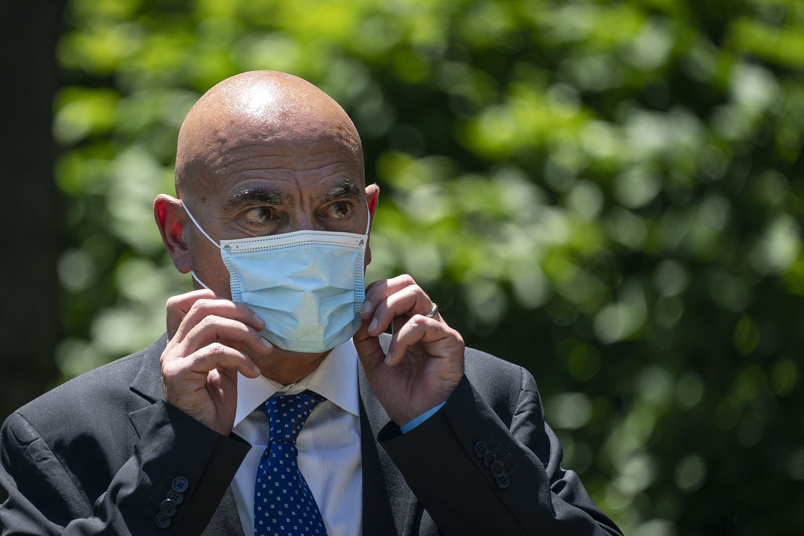 Moncef Slaoui listens as US President Donald Trump delivers remarks about coronavirus vaccine development in the Rose Garden of the White House on May 15 in Washington.