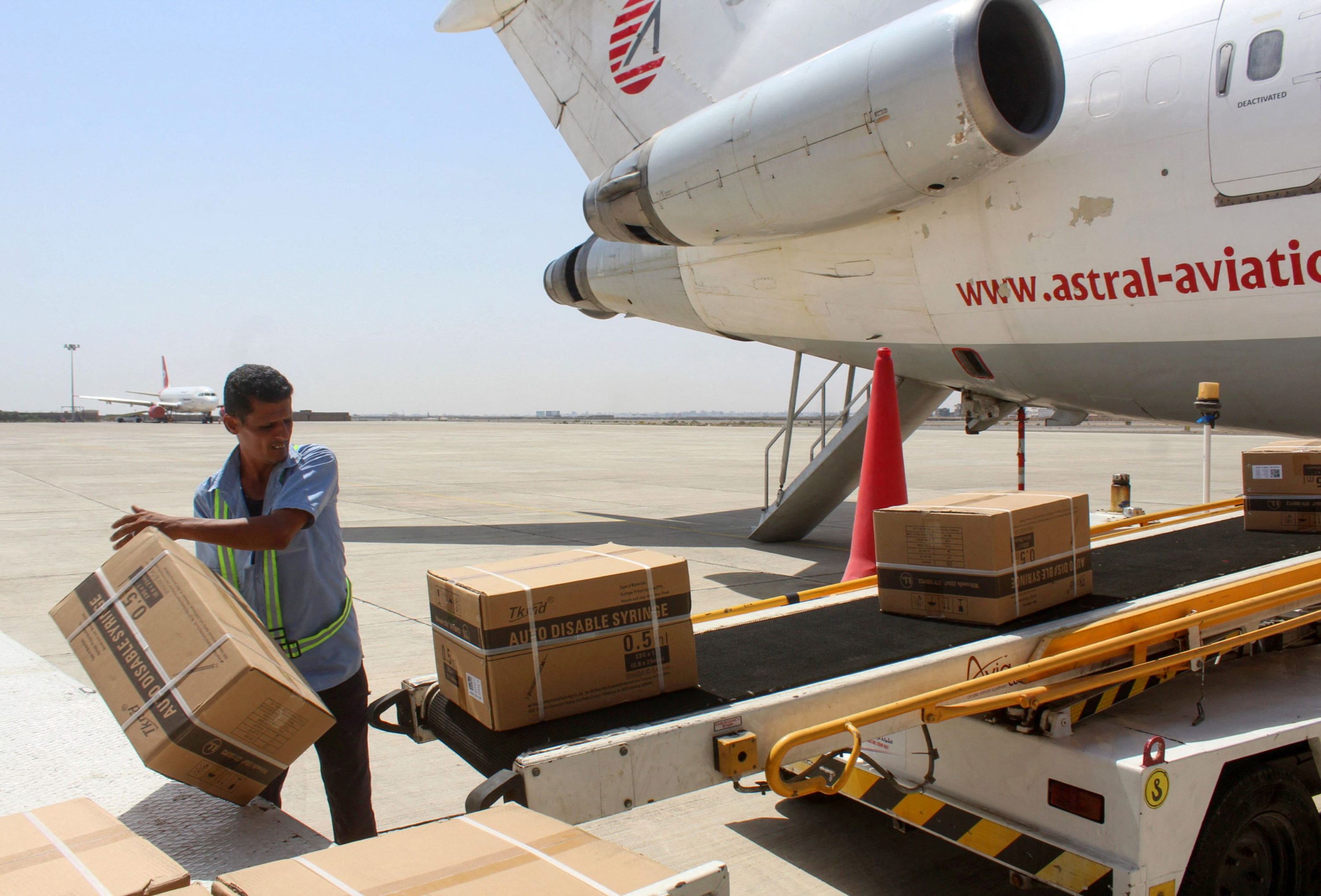 An employee unloads boxes from a plane that carried Yemen's first shipment of Covid-19 vaccines, via the international COVAX facility, at the airport of Yemen's southern port city of Aden on March 31.