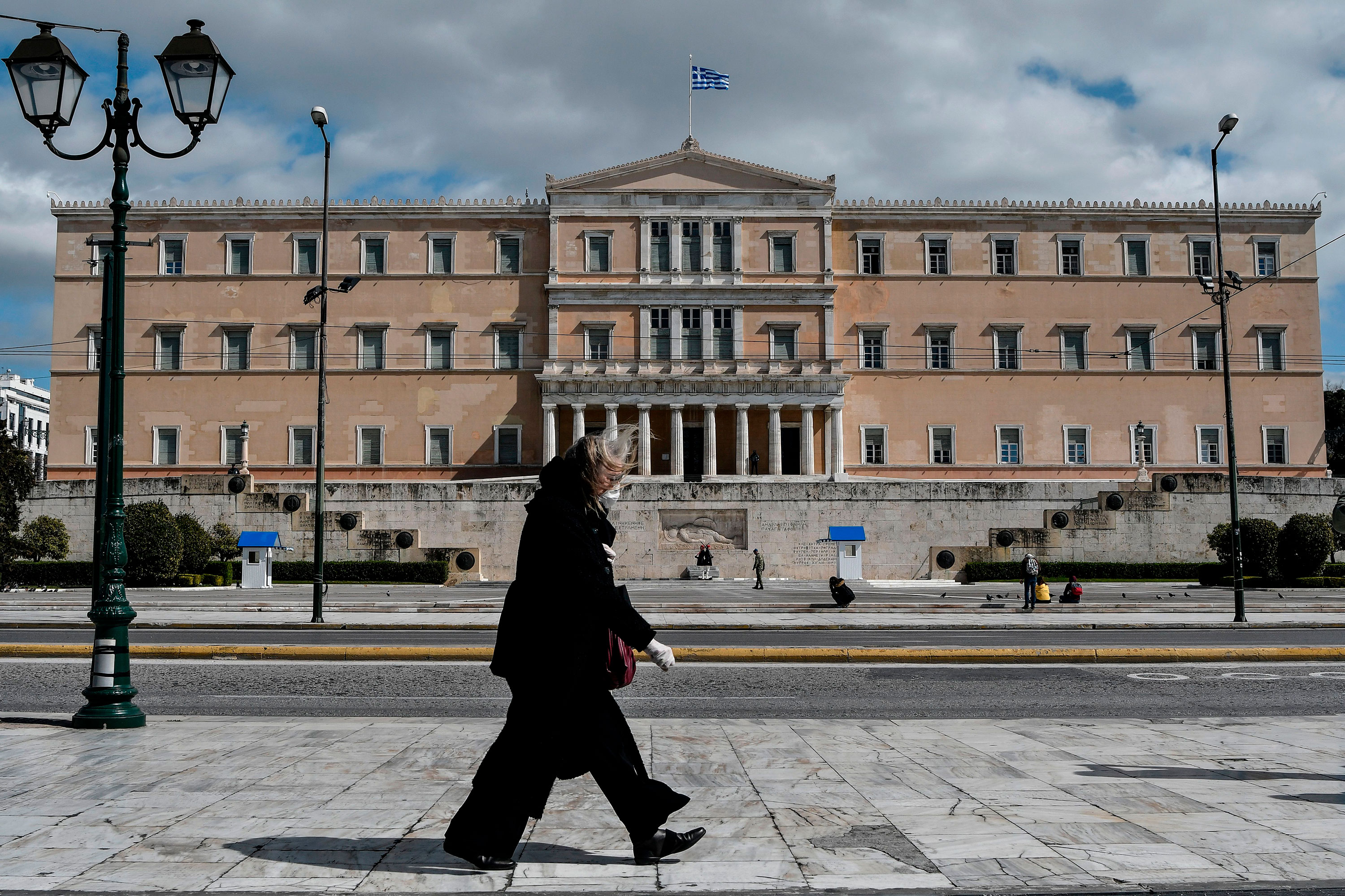 A woman walks past the empty Syntagma Square in Athens, Greece, on March 16.