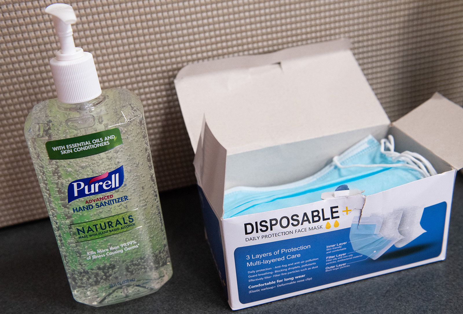 A bottle of Purell hand sanitizer and a box of disposable masks