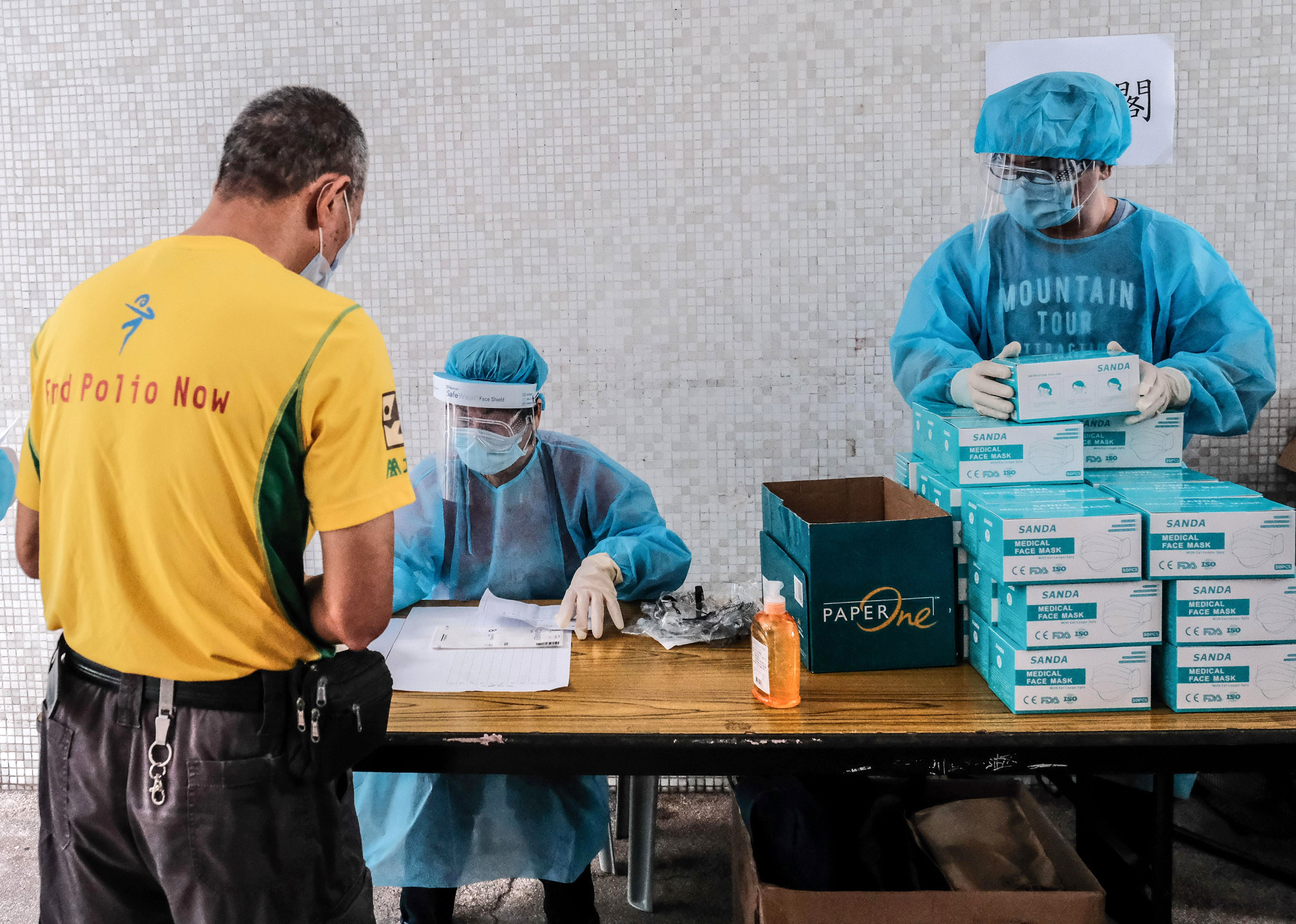 Medical workers hand out Covid-19 test kits at a residential block in Hong Kong on August 7.