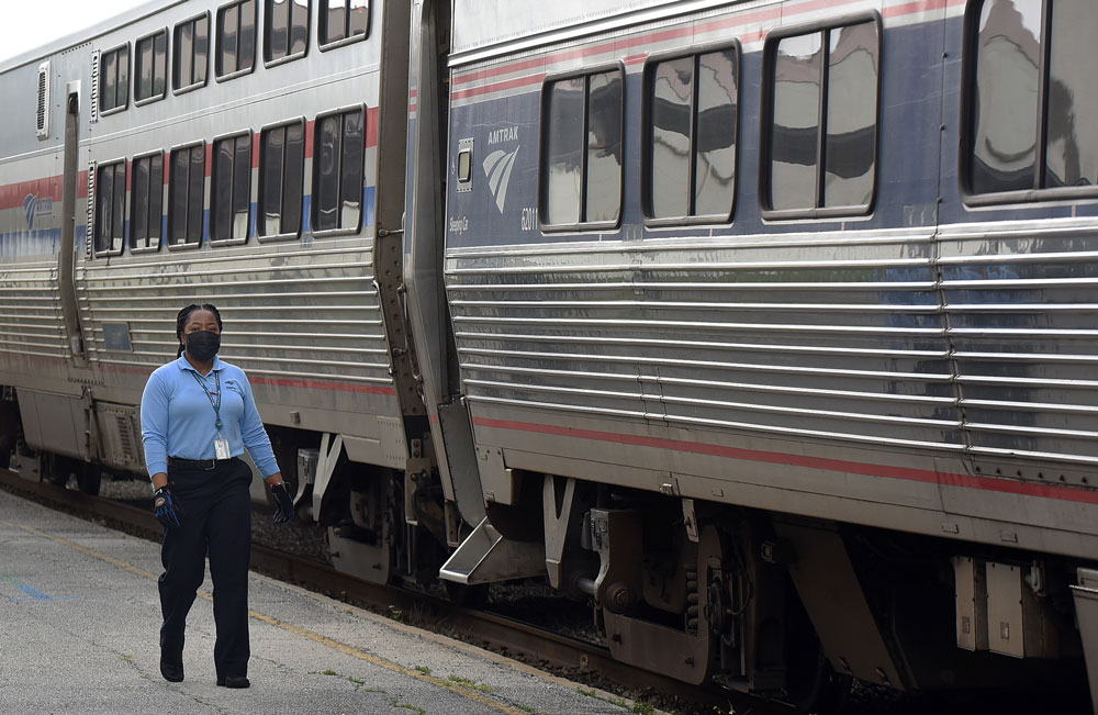 An Amtrak employee wearing a protective face mask walks alongside a nearly empty southbound Amtrak train as it arrives on April 15 in Orlando, Florida.