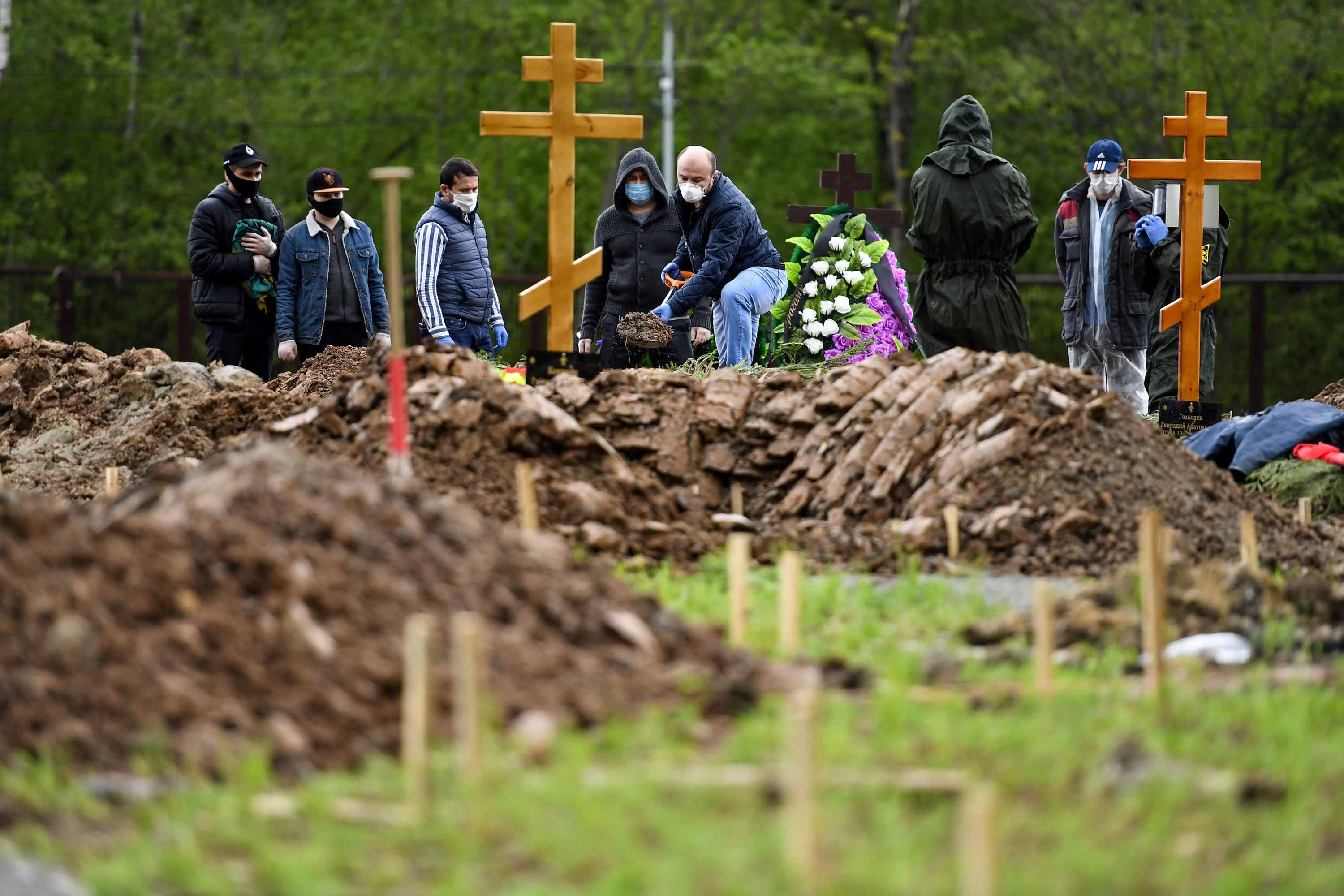 Mourners attend a burial ceremony of a coronavirus victim at a cemetery on the outskirts of Moscow, on May 15.