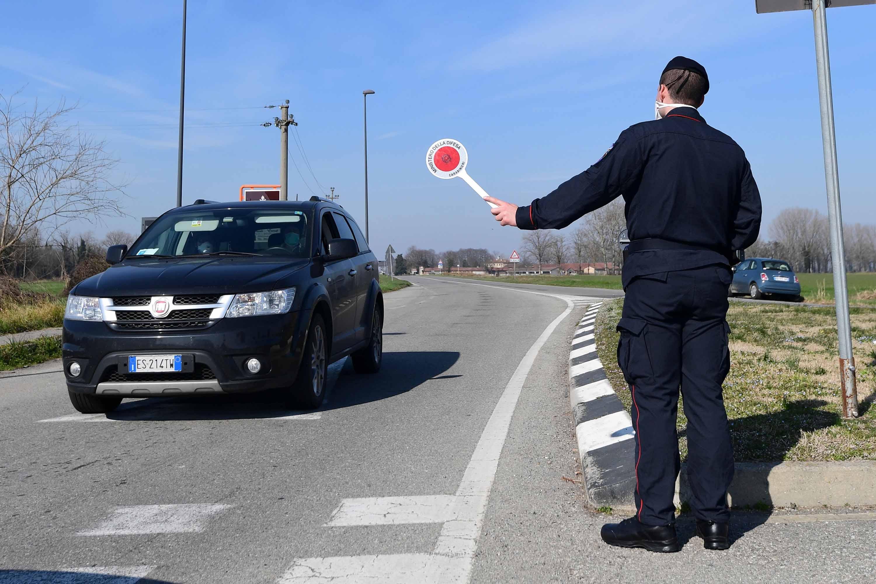 An Italian official stops a car at a police check-point near Castiglione d'Adda, southeast of Milan, on Monday.