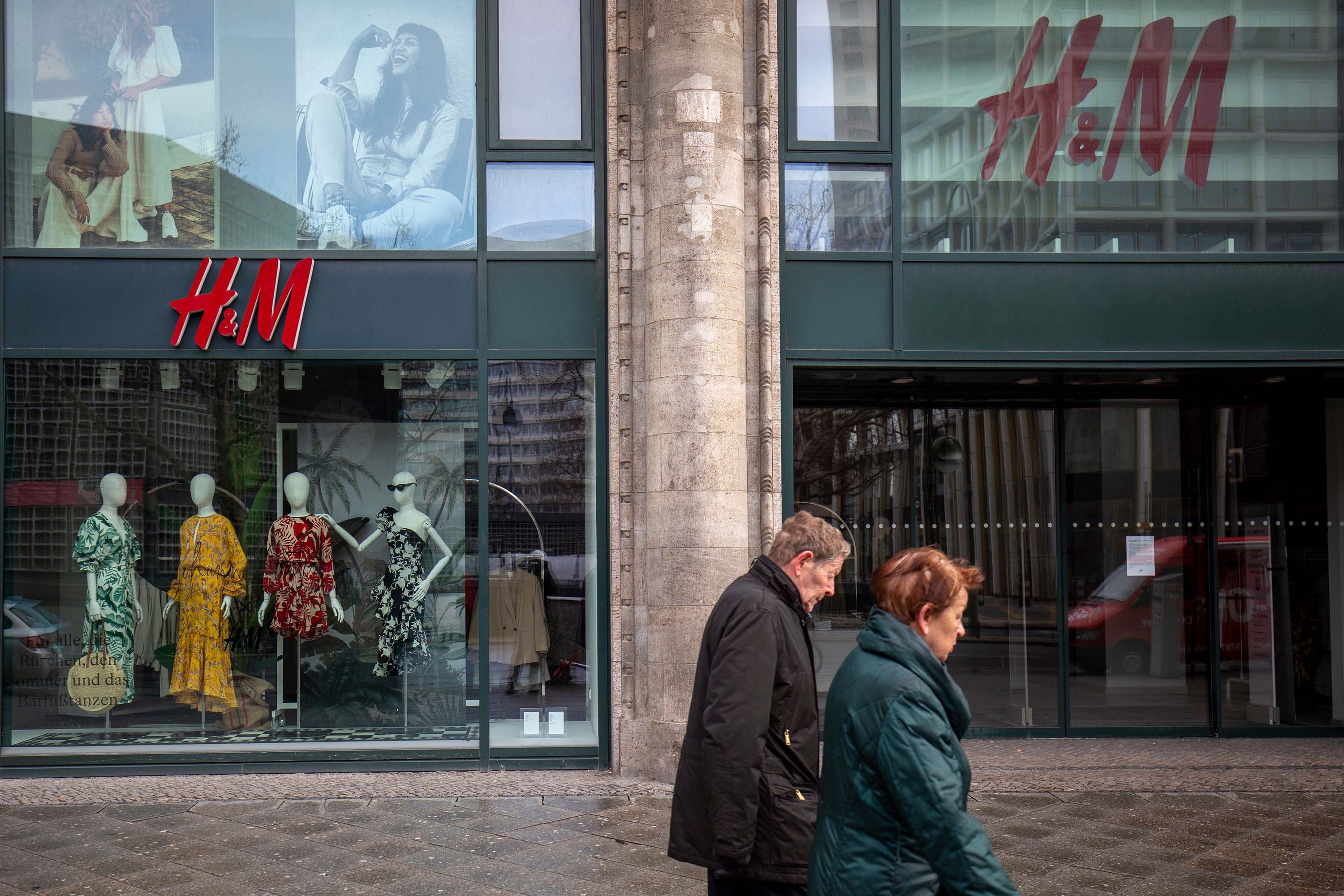 A couple walks past an H&M store in Berlin, Germany, on March 29.