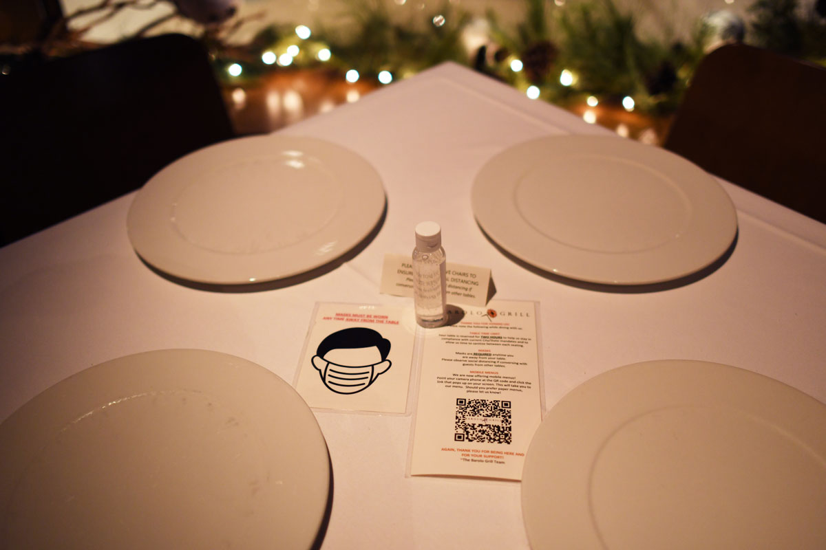 A hand sanitizer and reminders of coronavirus guidelines are placed on each table of Barolo Grill in Denver, Colorado on February 3.