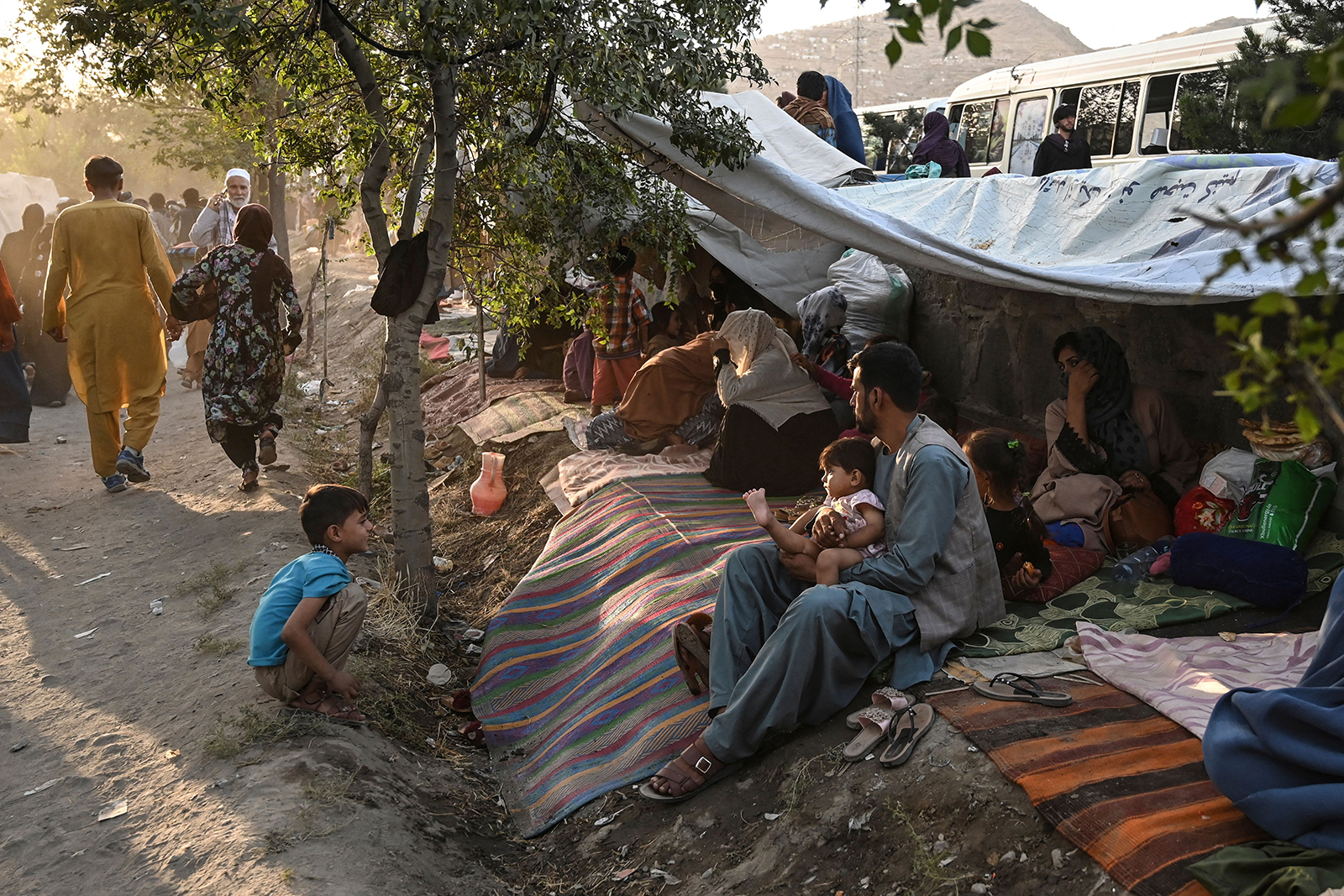 Internally displaced Afghan families, who fled from Kunduz, Takhar and Baghlan province due to battles between Taliban and Afghan security forces, sit in front of their temporary tents at Sara-e-Shamali in Kabul on August 11.