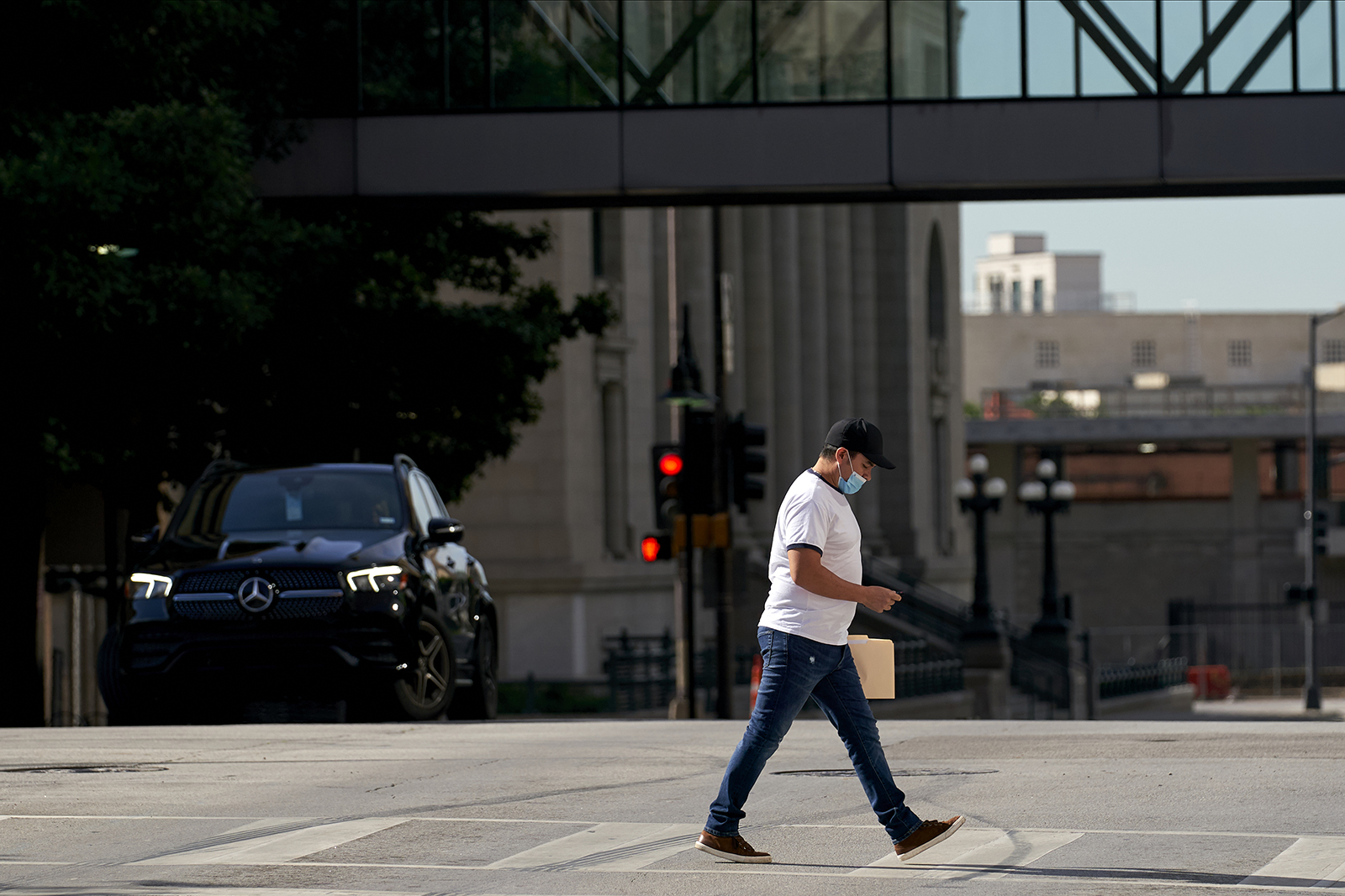 A pedestrian wearing a protective mask walks in downtown Dallas, Texas on Wednesday, May 27.