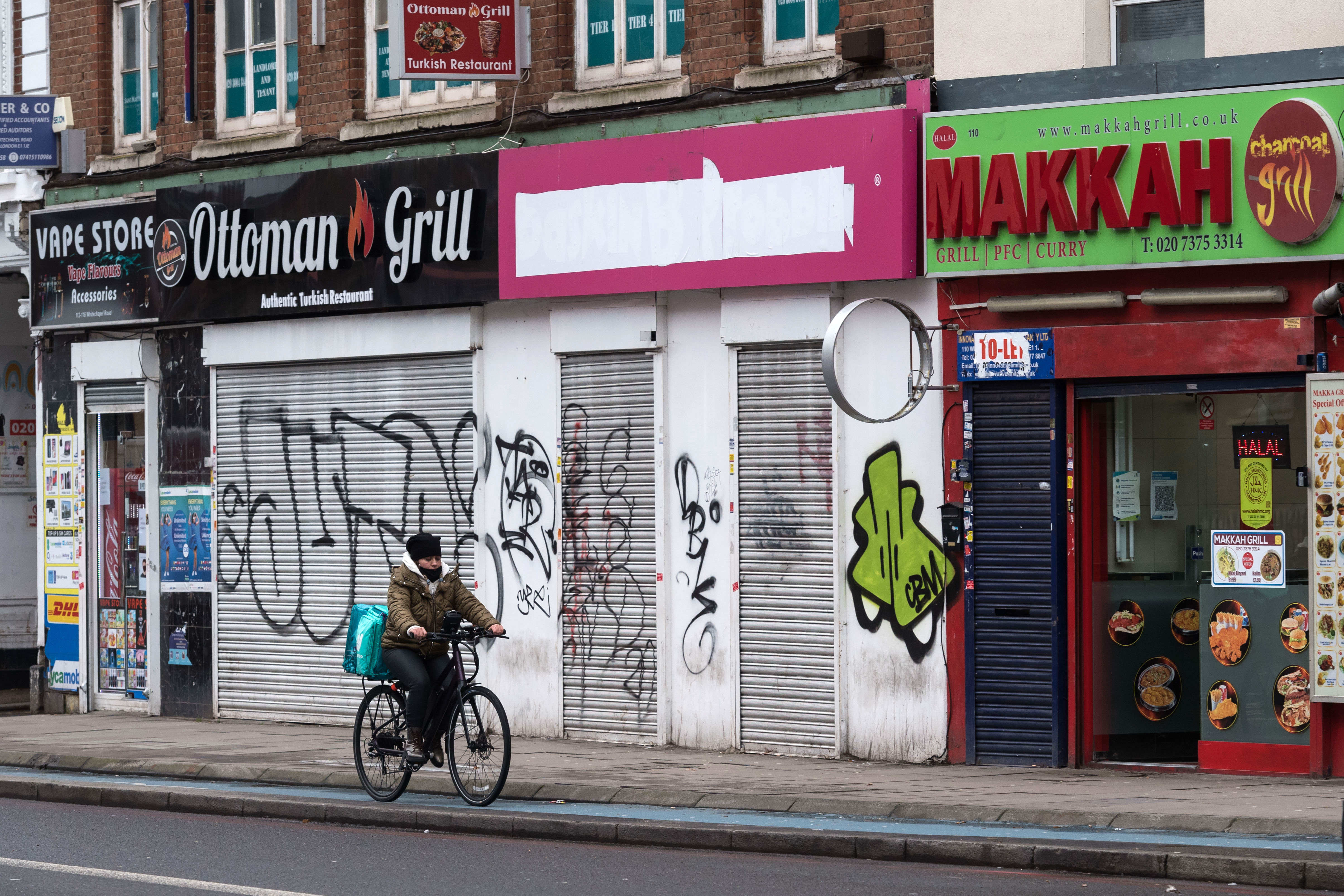 A person rides past some closed restaurants in London on February 1.