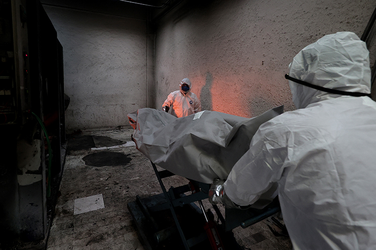 Crematorium workers place the body of a person who died of COVID-19 into the oven to be cremated at the San Isidro Crematorium in Azcapotzalco,  on Wednesday, July 15,  in Mexico City.
