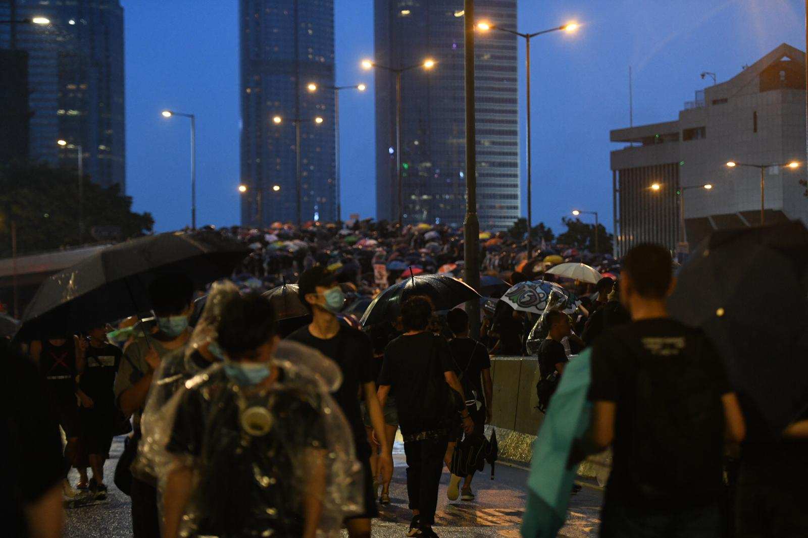Protesters marching from Wan Chai to Central district as night falls.