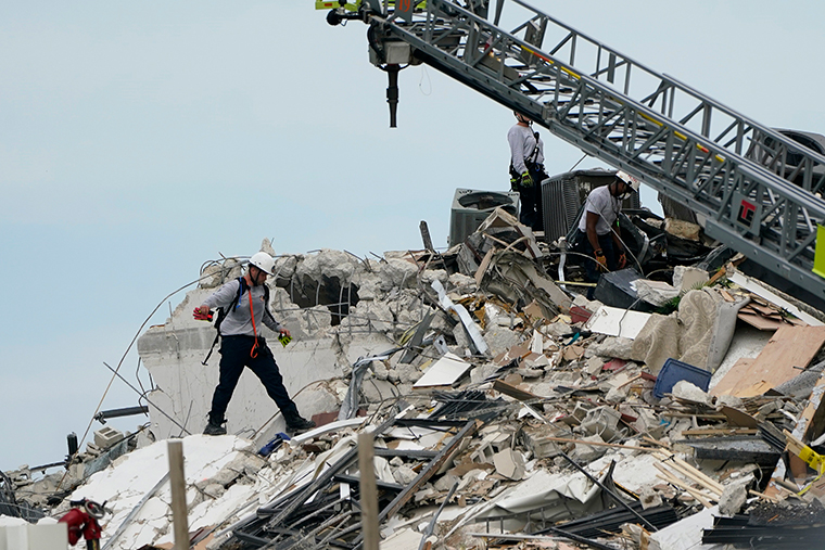 A rescue worker walk among the rubble of the collapsed building, Thursday, June 24.