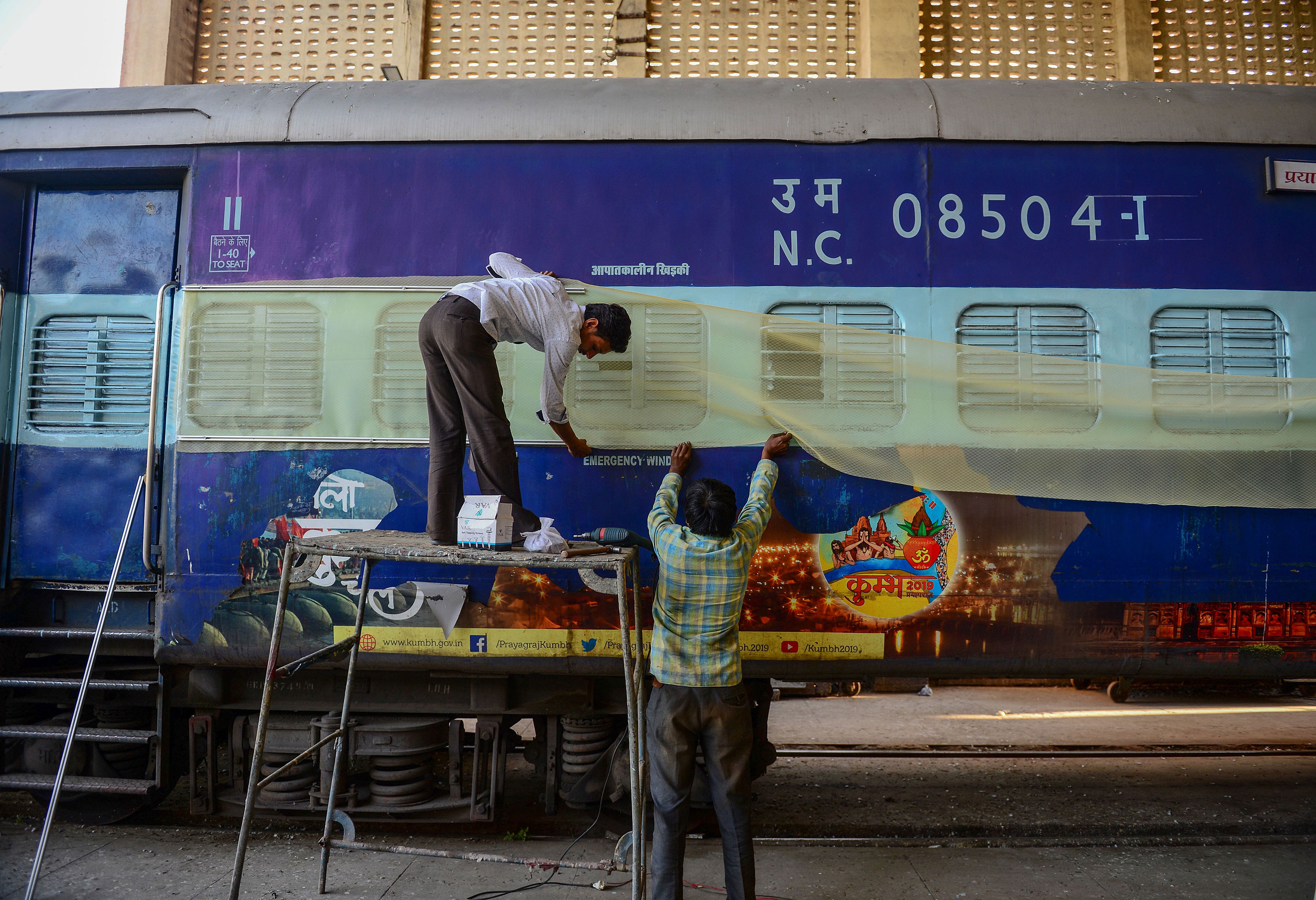 Laborers work on train coaches that will be used as temporary isolation wards in preparation for coronavirus-infected patients at a workshop in Allahabad on April 4, 2020.