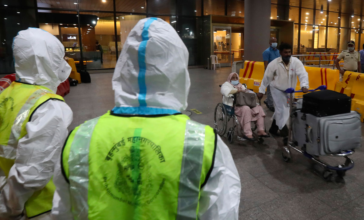 Indian municipal workers in personal protective equipment watch as passengers arrive from the United Kingdom, at Chhatrapati Shivaji Maharaj International Airport in Mumbai on December 22.