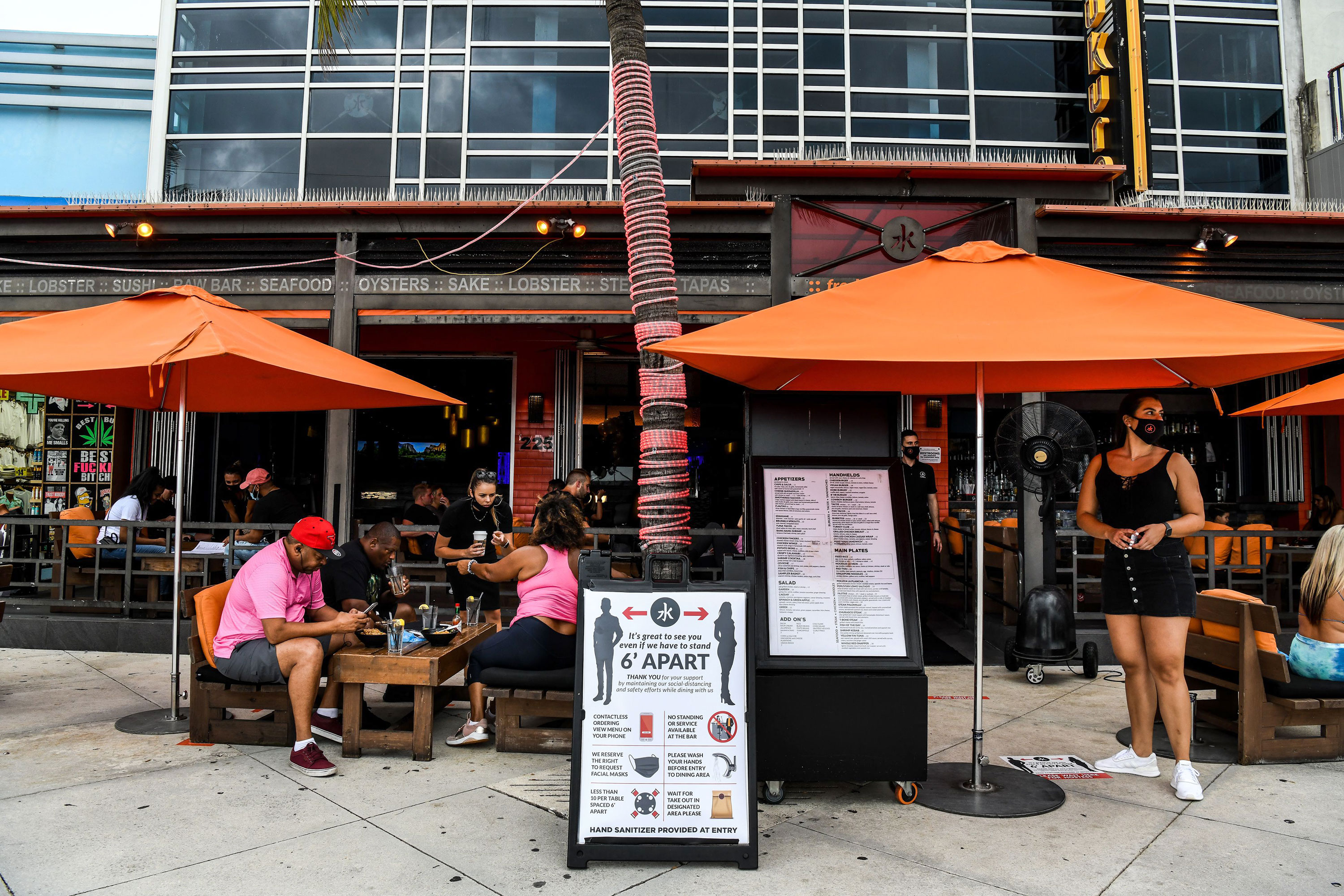 People eat outside of a restaurant in Fort Lauderdale, Florida, on May 18.